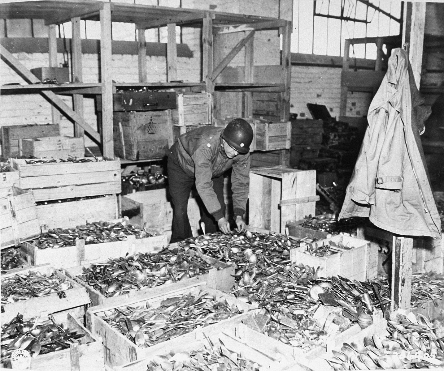 An American soldier sorts through crates of silverware taken from prisoners in Buchenwald.  The crates were hidden in a nearby cave along with other boxes of confiscated belongings.