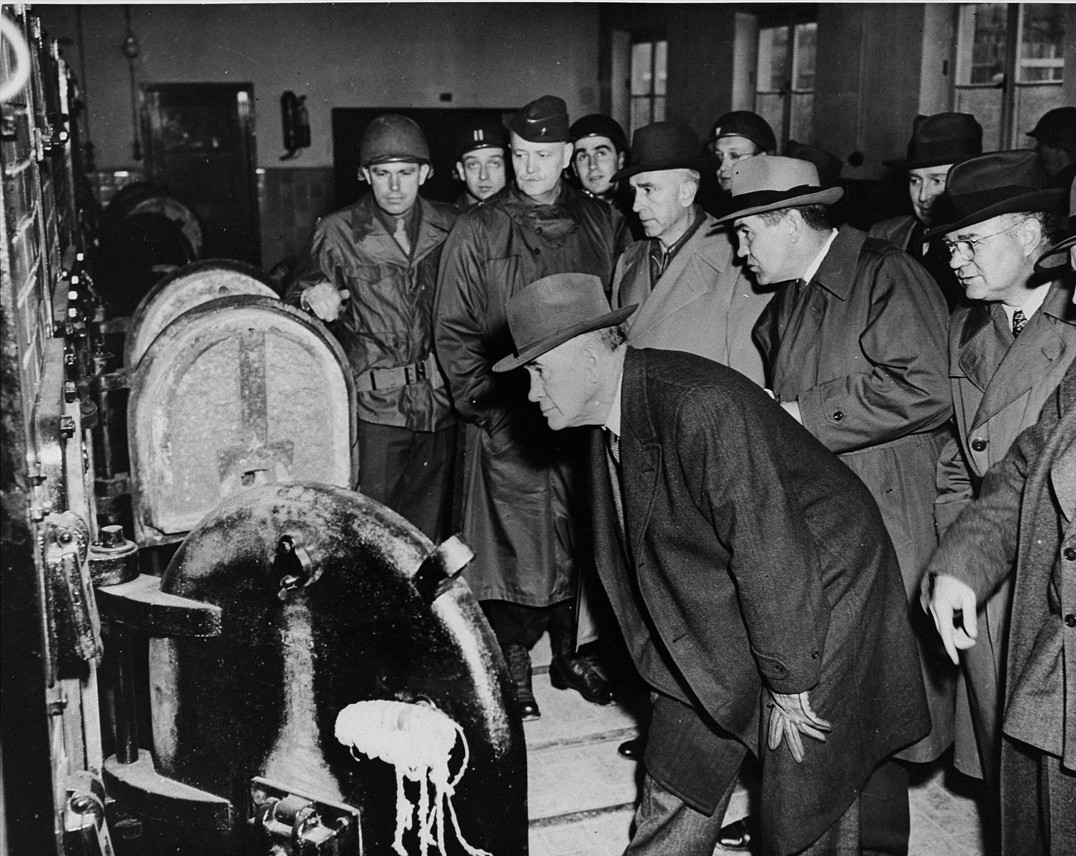 American congressmen view the open ovens in the Buchenwald crematorium during an inspection of the newly liberated concentration camp.  Pictured from left to right are: Senator Alben W. Barkely (D.Ky), Representative Edward V. Isac (D.CA.), Representative John M. Vorys (R. OH.), Representative Dewey Short (R. MO.), Senator C. Wayland Brooks, (R. IL.), and Senator Kenneth S. Wherry (R. NB).