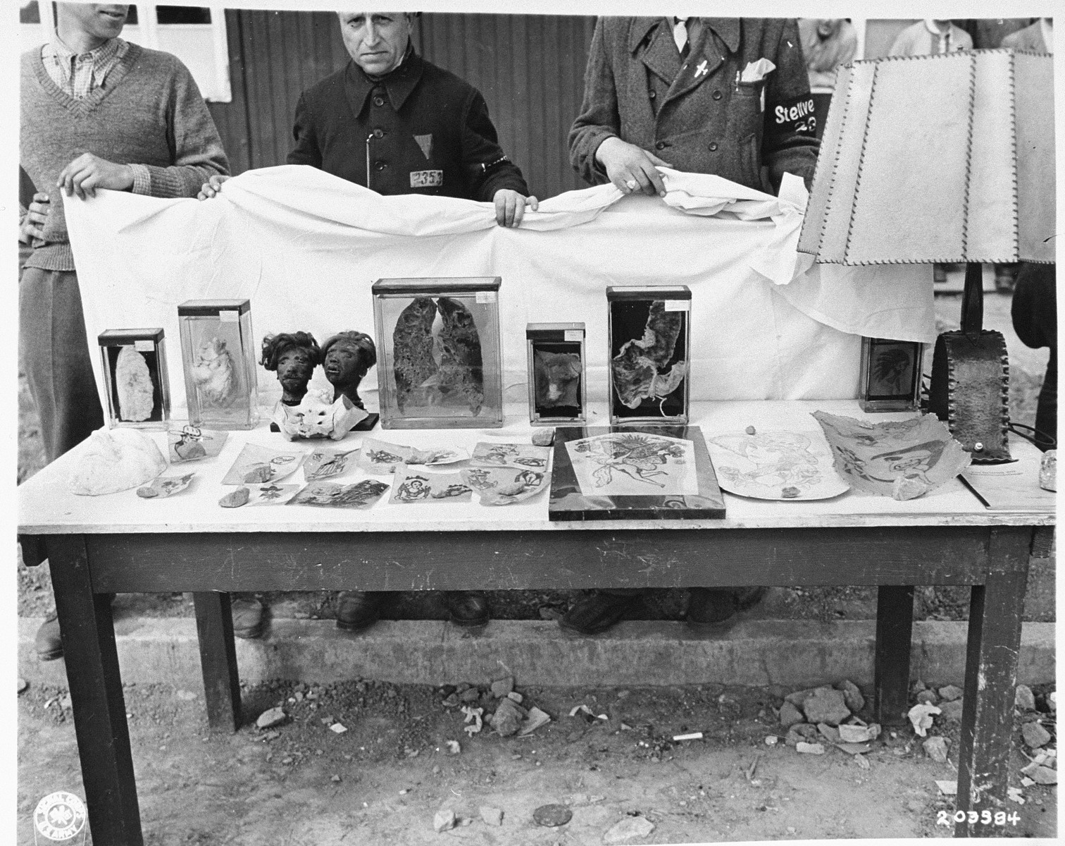 An exhibit of human remains and artifacts retrieved by the American Army from a pathology laboratory run by the SS in Buchenwald.    These items were used as evidence of SS atrocities in the Buchenwald war crimes trial held at Dachau, Germany.  The two shrunken heads are from Polish prisoners who were recaptured after escaping from the camp and executed.
