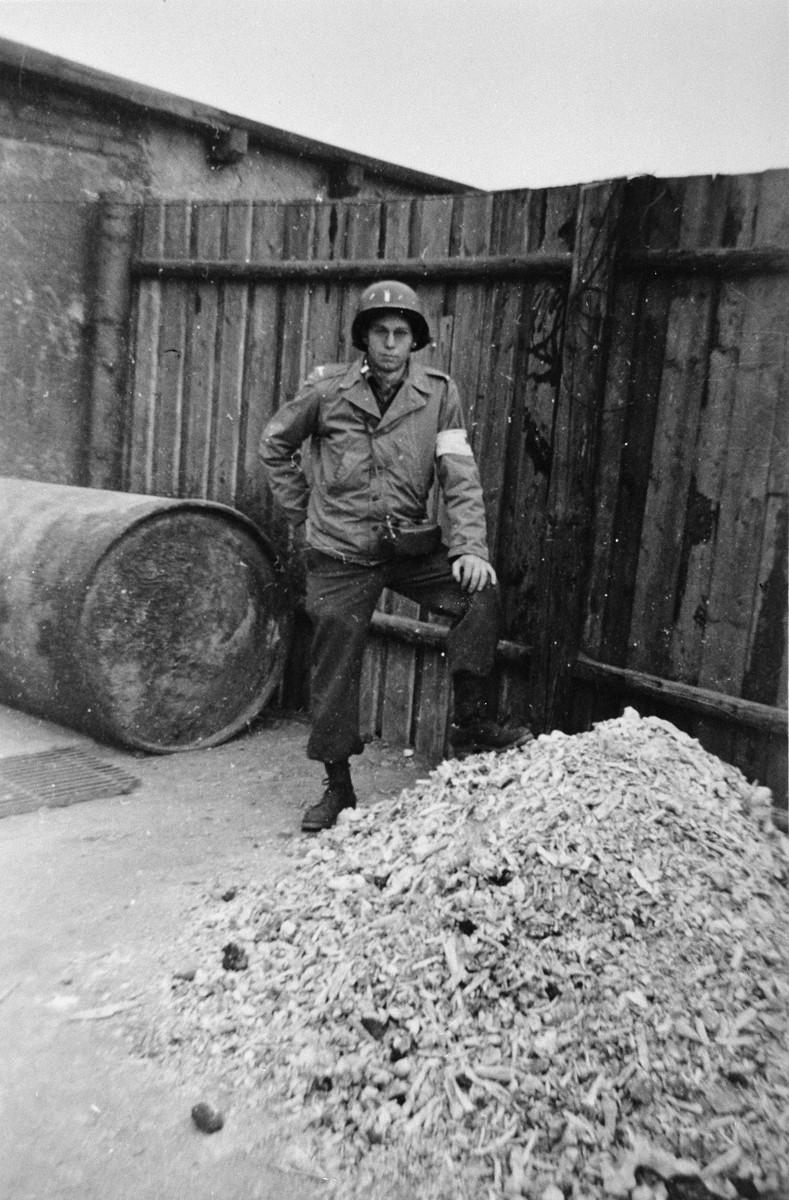 An American Captain in the Red Cross poses next to a pile of bones during an inspection of Buchenwald.