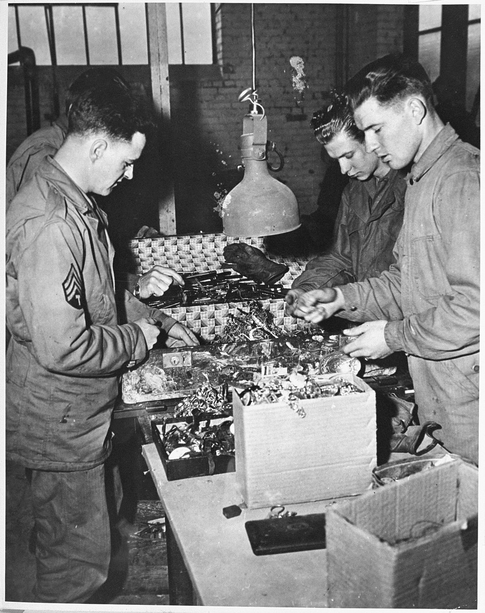 American soldiers from the First Army sorting through jewelry, including gold fillings, taken by the SS from prisoners in the Buchenwald concentration camp.