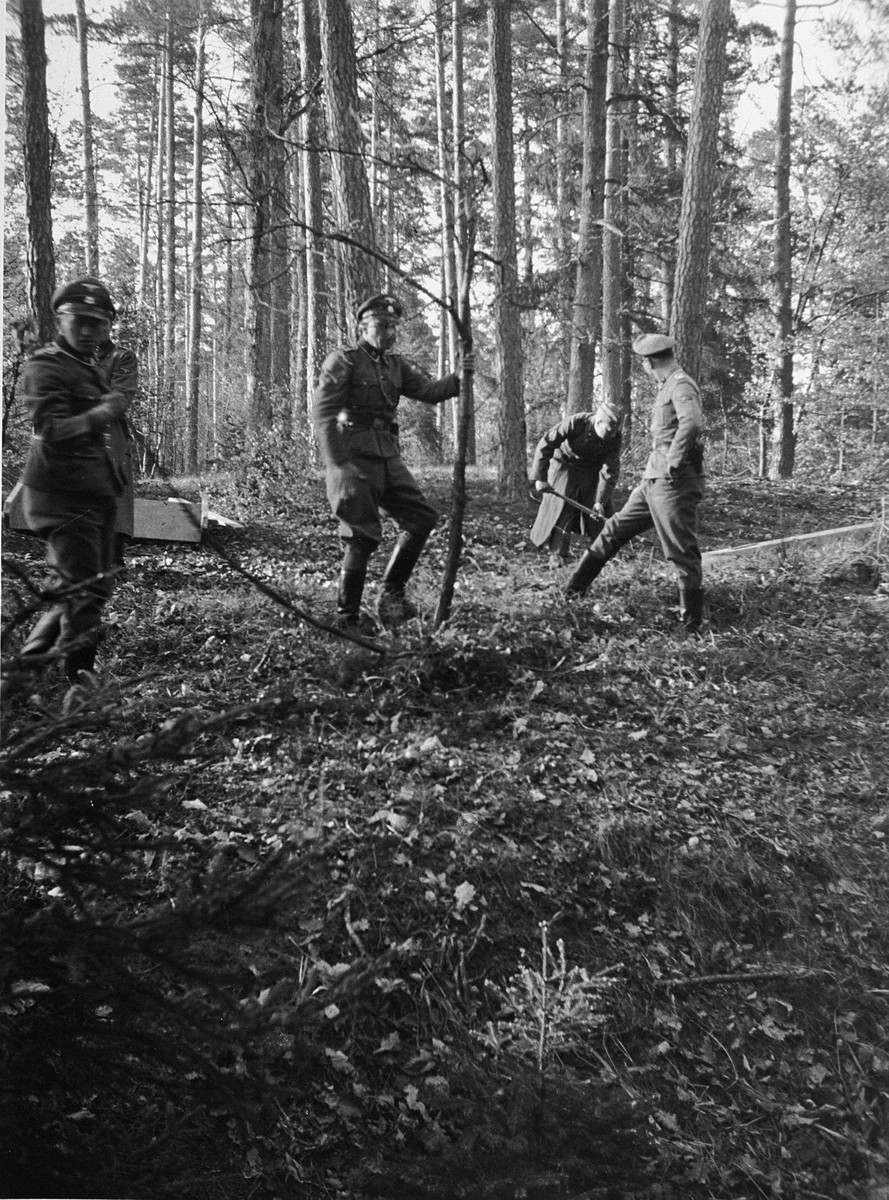SS officers clearing an area to erect a gallows in the forest near Buchenwald.