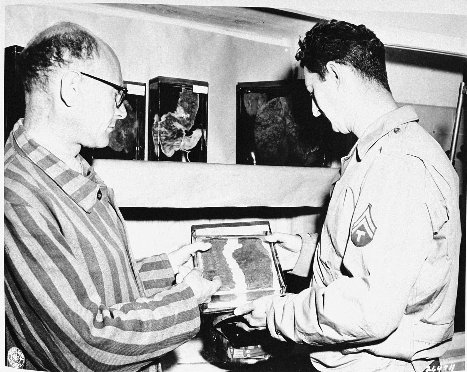 A guide shows jars containing human organs removed from prisoners in Buchenwald to Jack Levine, a techical sgt., 5th Armored Division.