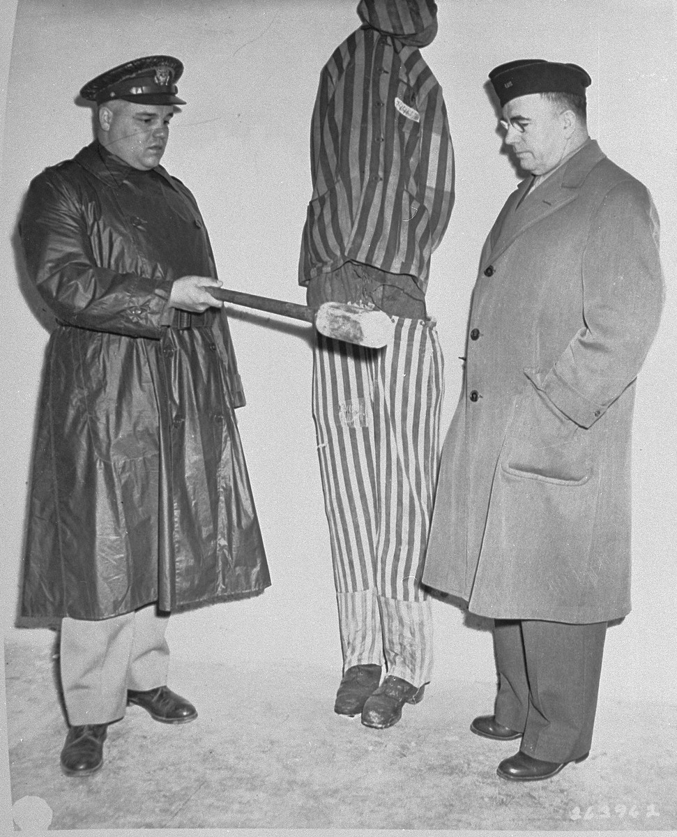 G. Bromley Oxnam (right), the Methodist bishop of New York and President of the Federated Council of Churches of Christ in America, views a demonstration of how prisoners were tortured in Buchenwald during an inspection of the newly liberated concentration camp by U.S. Army chaplains.