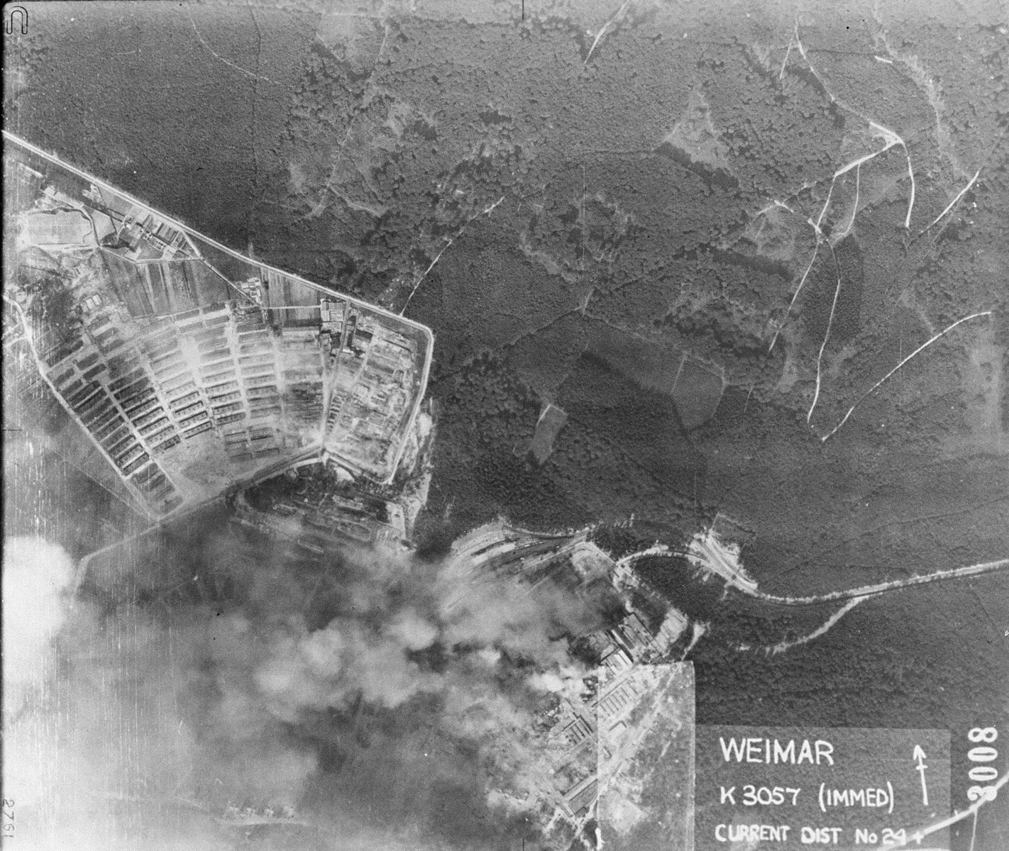 An aerial photograph of Buchenwald concentration camp showing the destruction of the munitions factory and storage area of the camp by American bombers.