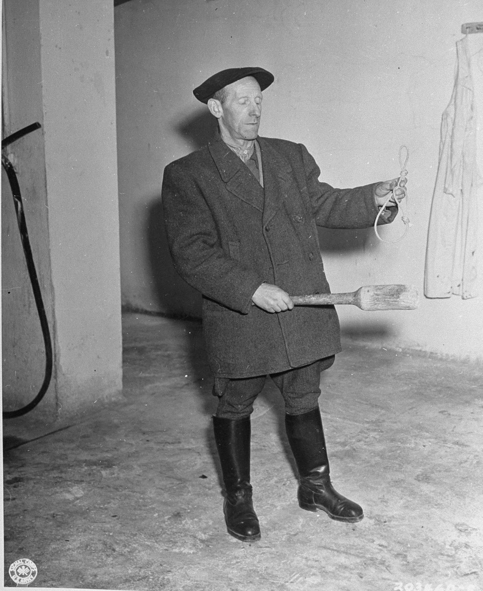 The new caretaker of Buchenwald concentration camp displays a noose and club used by the SS to murder prisoners.  He was appointed by Third Army officers in the Military government.