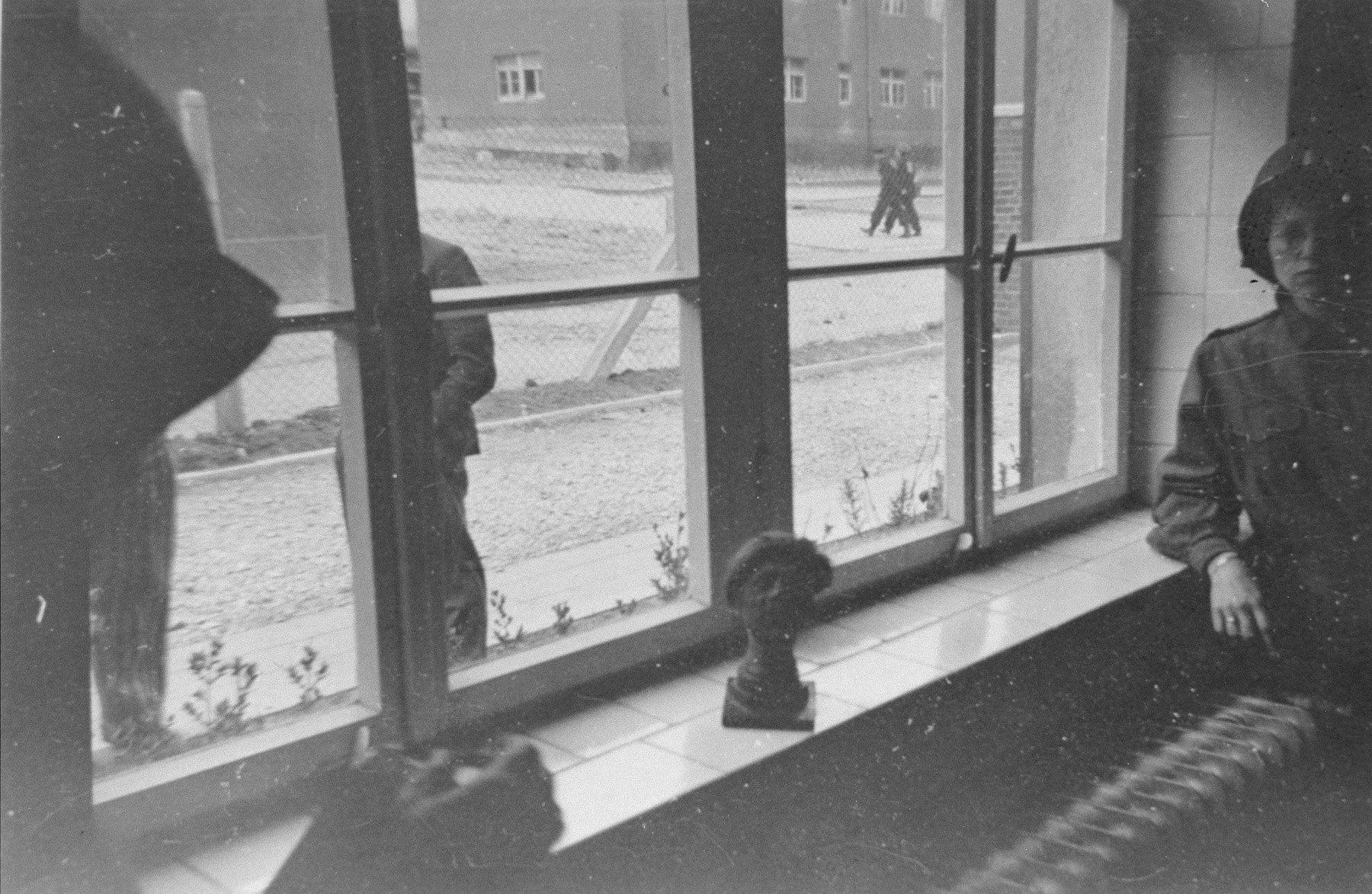 An American soldier stands next to a shrunken head perched on a windowsill in a building in Buchenwald.