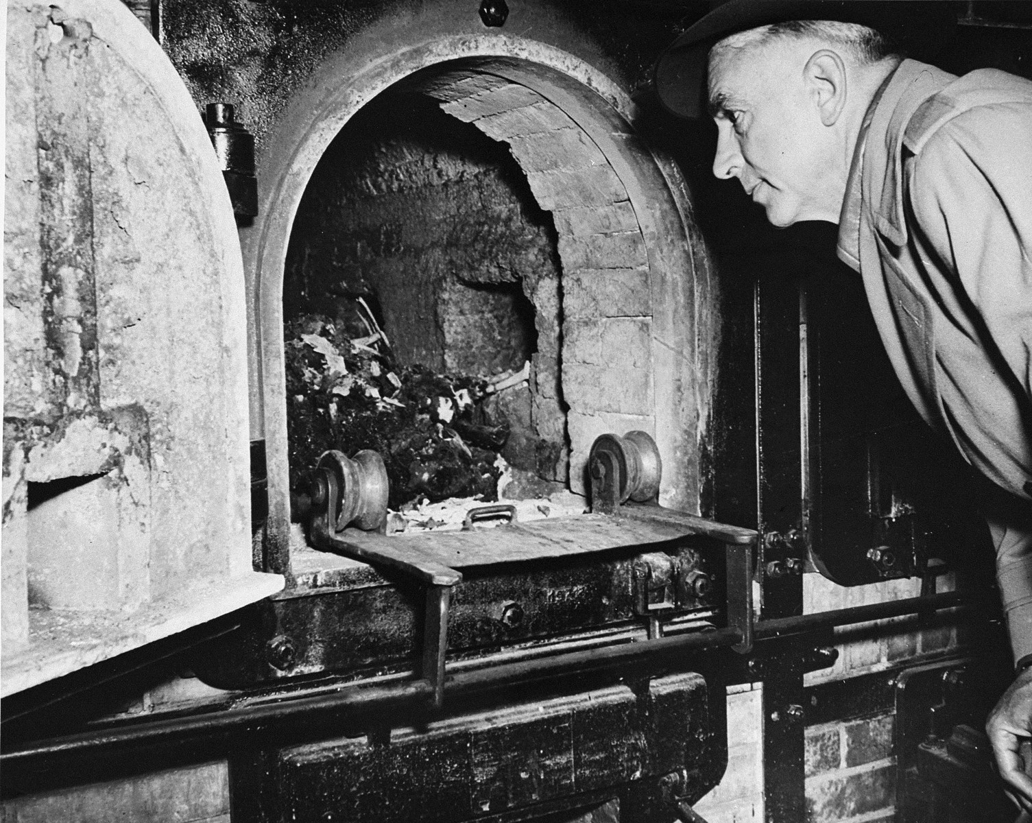 Congressman Ed V. Izak of California, a member of a Congressional delegation that traveled to Germany to view evidence of Nazi atrocities, looking at human remains in a crematorium oven.