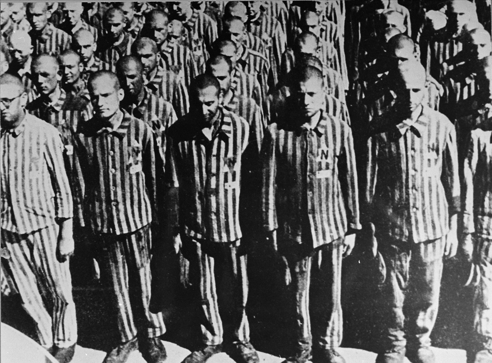 "Dutch Jews wearing prison uniforms marked with a yellow star and the letter ""N"", for Netherlands, stand at attention during a roll call at the Buchenwald concentration camp.  See also w/s 59007."