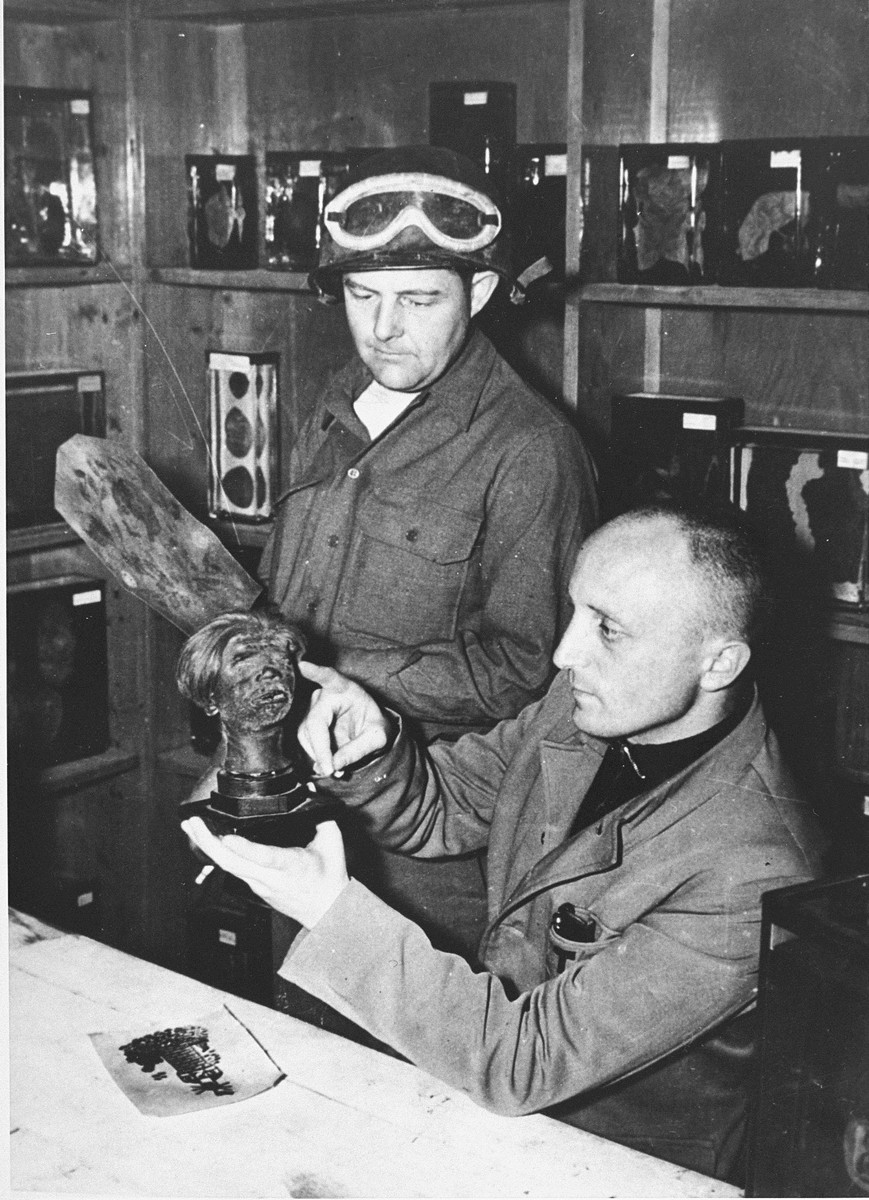 A Czech scientist and Wendell Birmingham, an American soldier, examining a shrunken head in Buchenwald after liberation.  The Czech was a former prisoner who was forced to dissect cadavers in Buchenwald.  The head is of an executed Pole, which, on the instructions of the SS, had been shrunken according to the method used by the Jivaro Indians of Ecuador.  Visible behind them are pieces of tanned, tattooed human skin and organs, all stored in the pathology laboratory where the SS forced staff workers to dissect the bodies of dead prisoners and make a collection of abnormalities.