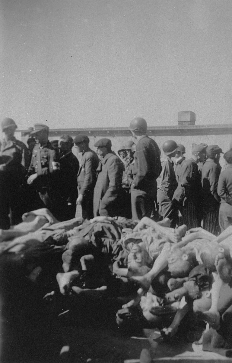 Survivors and American soldiers, including a German POW, inspect a pile of corpses in Buchenwald.