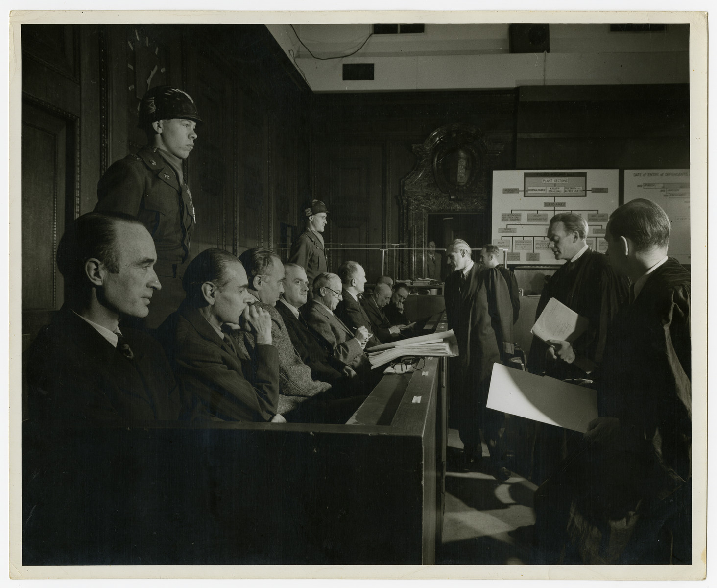 Close-up view of the defendants of the Krupp case.  Behind them are military police.  Seated in the front left is the chief defendant Alfred Krupp von Bohlen.  In the back is a poster showing organizational structures.