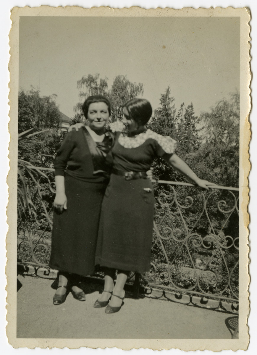 Ida and Lottie Cohn pose in front of a metal fence.
