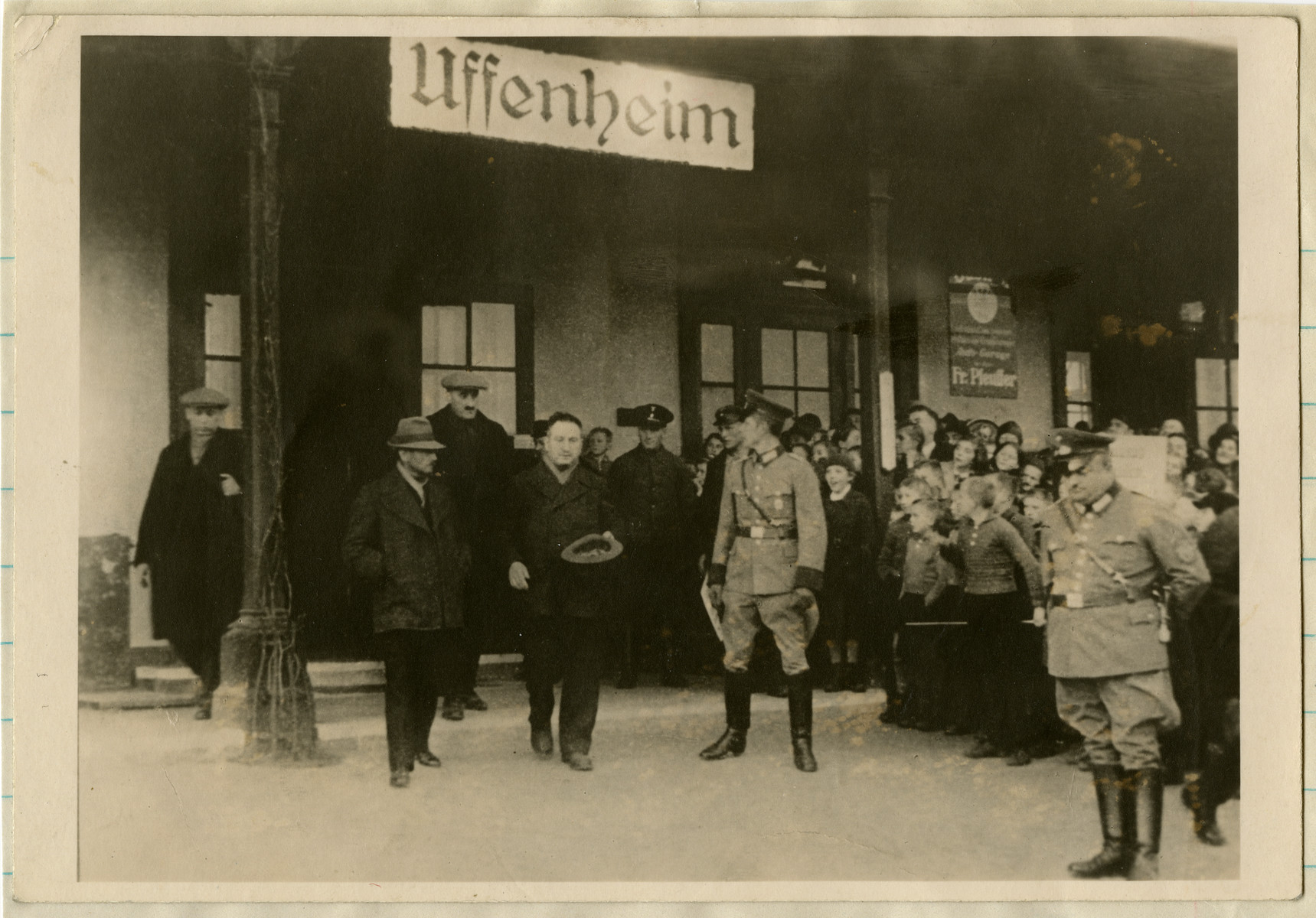 German police stand guard as Jews are driven out of Uffenheim while a group of children gathers to stare at what is transpiring.