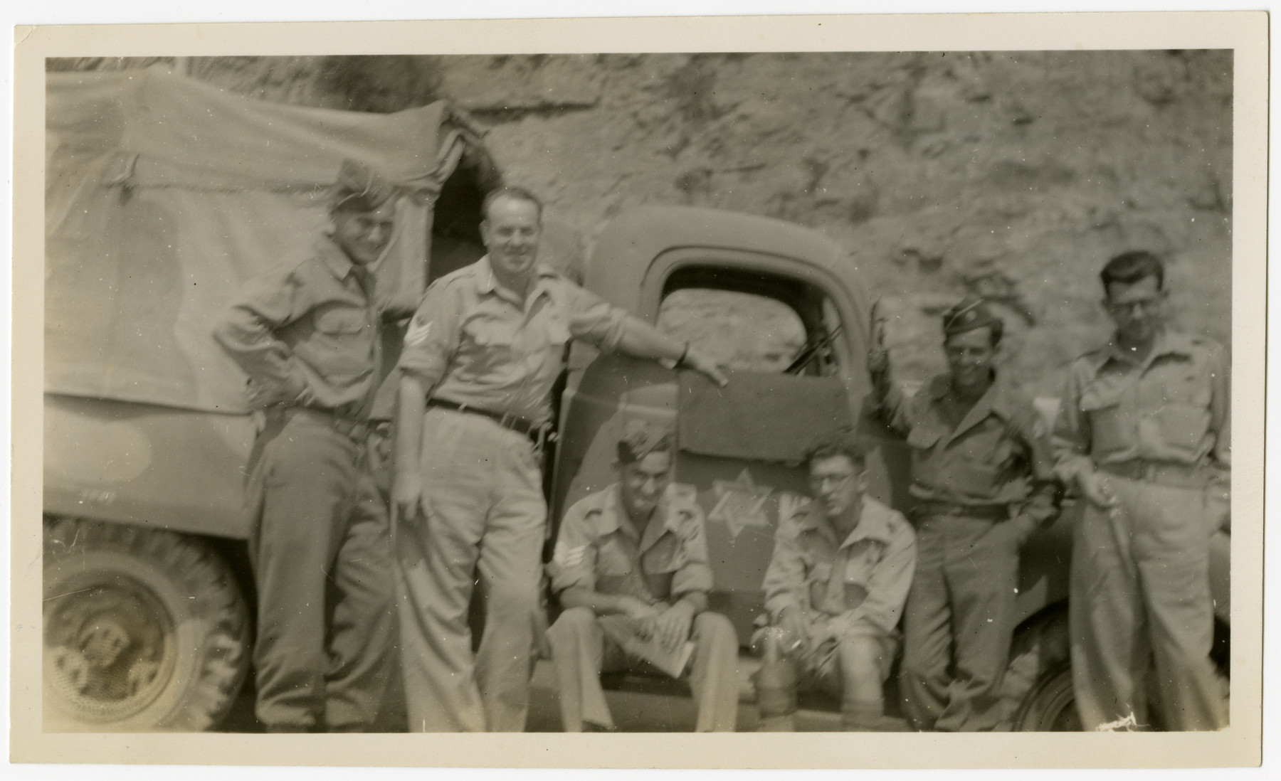 American Jewish soldiers and members of the Jewish Brigade pose together in front of a miltary truck decorated with a Star of David.