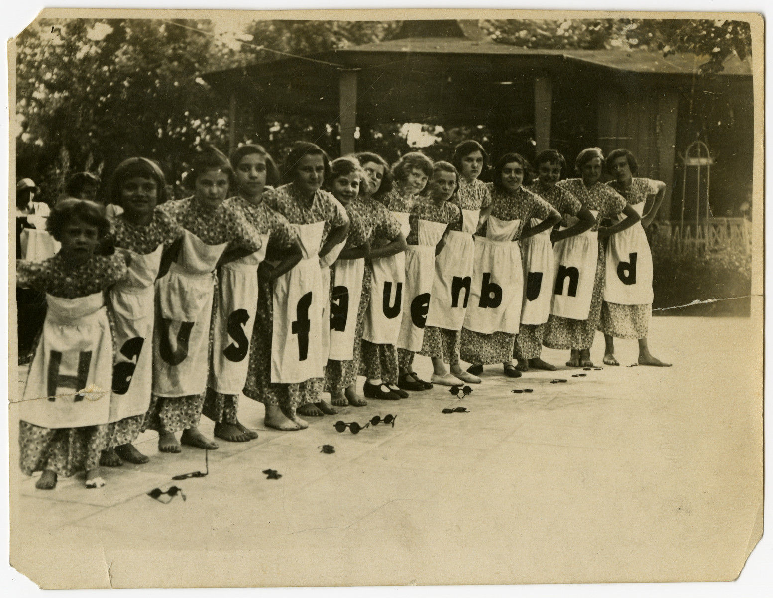 """German school girls and members of the Hausfrauenbund (Housewife's club) pose wearing alphabet aprons.  Marian Cohn is pictured fourth from the right with the """"B"""" apron."""