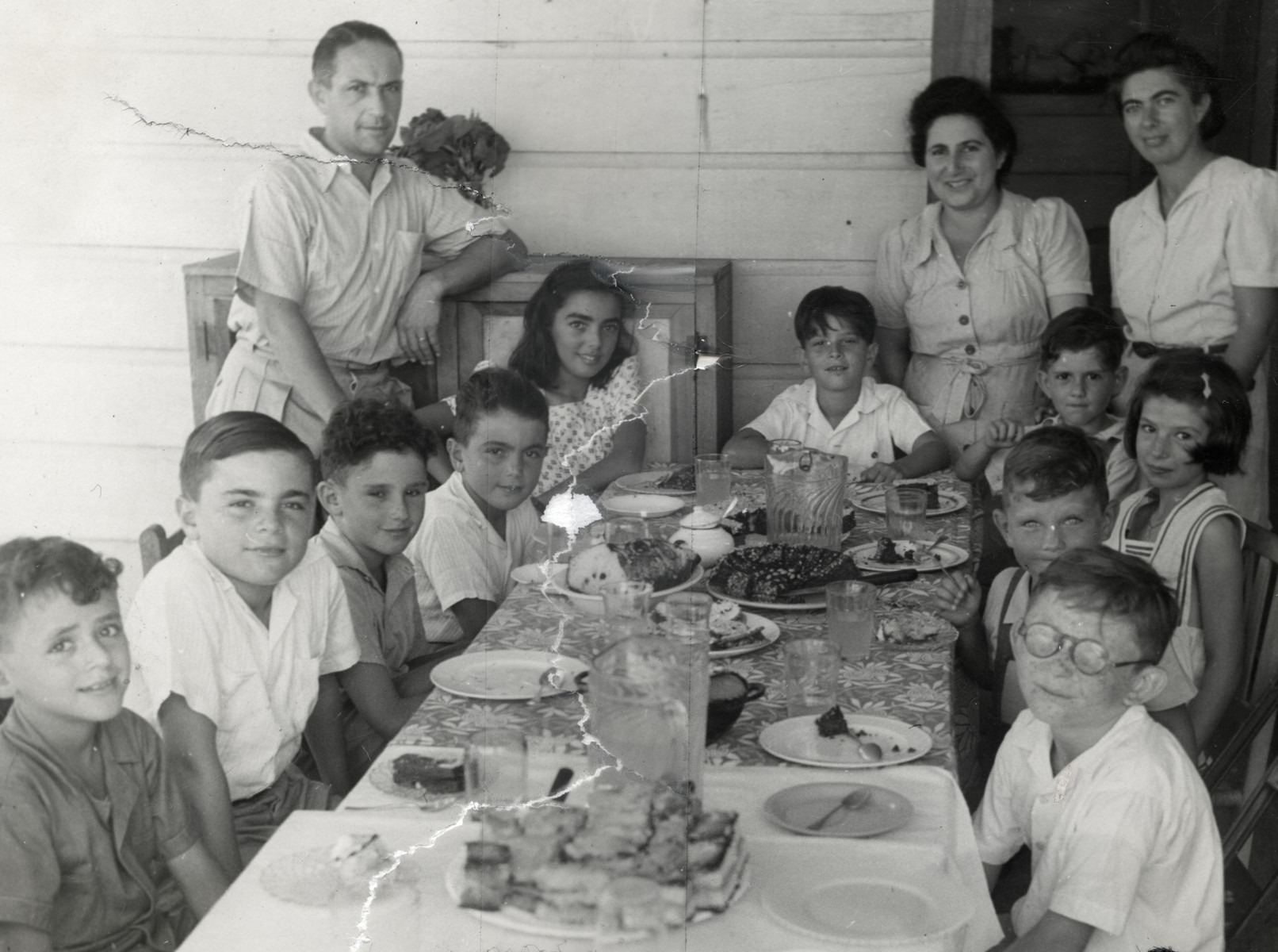School children sit down for a meal in the Sosua refugee colony.    Seated on the left (front to back) are Danny Herzberg, Alex Salomon, unidentified, and Marcel Salomon.  Mr. Bein, one of the directors, is standing on the left).  Henry Danziger is seated in the front, right.