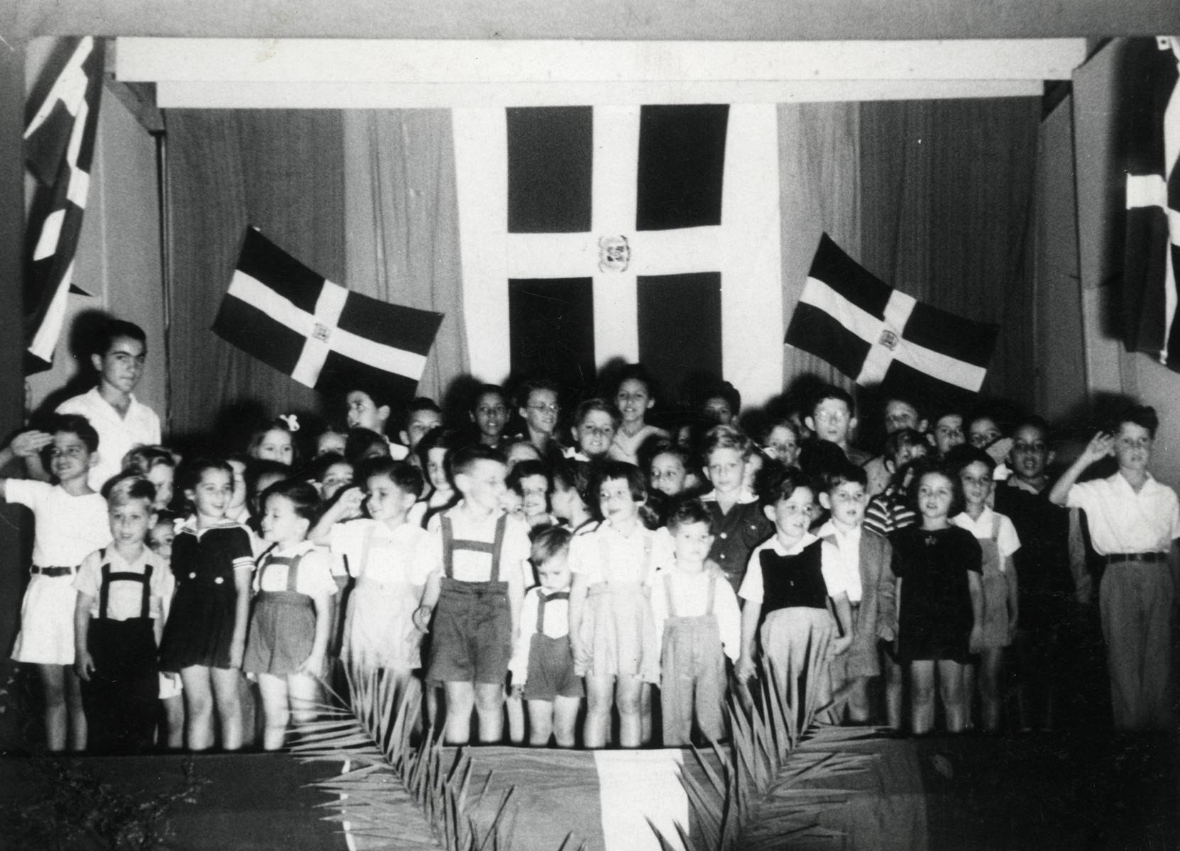 Young children stand in front of Dominican flags at a ceremony in their school in Sosua.    Teenager Marcel Salomon stands behind them on the left.