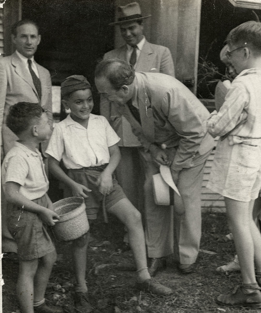 School children meet with the author Emil Ludwig in the Sosua refugee colony.  Marcel Salomon is pictured second from the left.  Emil Ludwig is leaning over him.  Henry Danziger is on the right.  In the back are Mr. Bein (a director of the school) and a representative of the Dominican government [probably Manuel de Moya Alonsa who accompanied Ludwig on this tour].