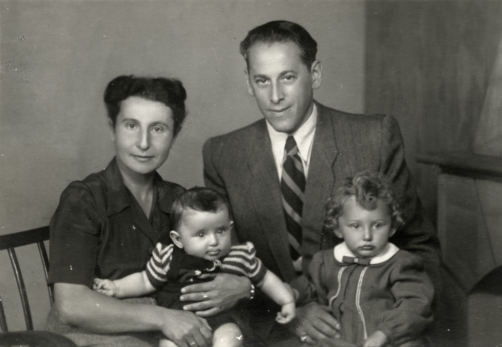 Postwar studio portrait of the Goldberg family in Walbrzych, Poland.  Elze Goldberg is holding their baby Chava (Eva) and Emil is holding their older daughter Lea.