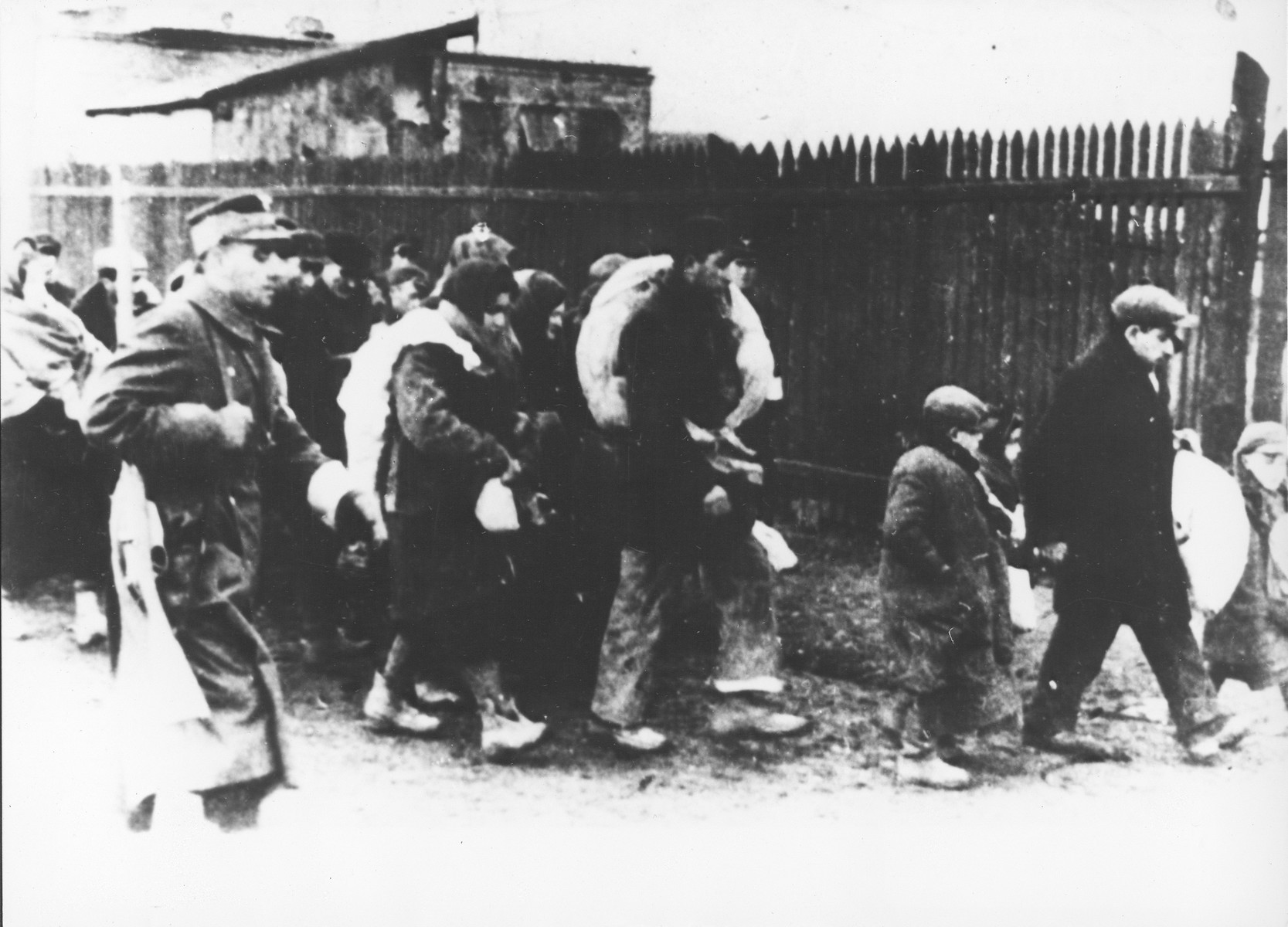 Jews are marched through town carrying bundles during a deportation action from Plonsk.