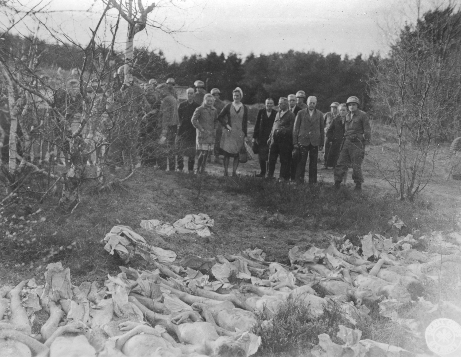 Under the supervision of American soldiers, German civilians view the bodies of female prisoners exhumed from a mass grave near the Helmbrechts concentration camp, a sub-camp of Flossenbuerg.