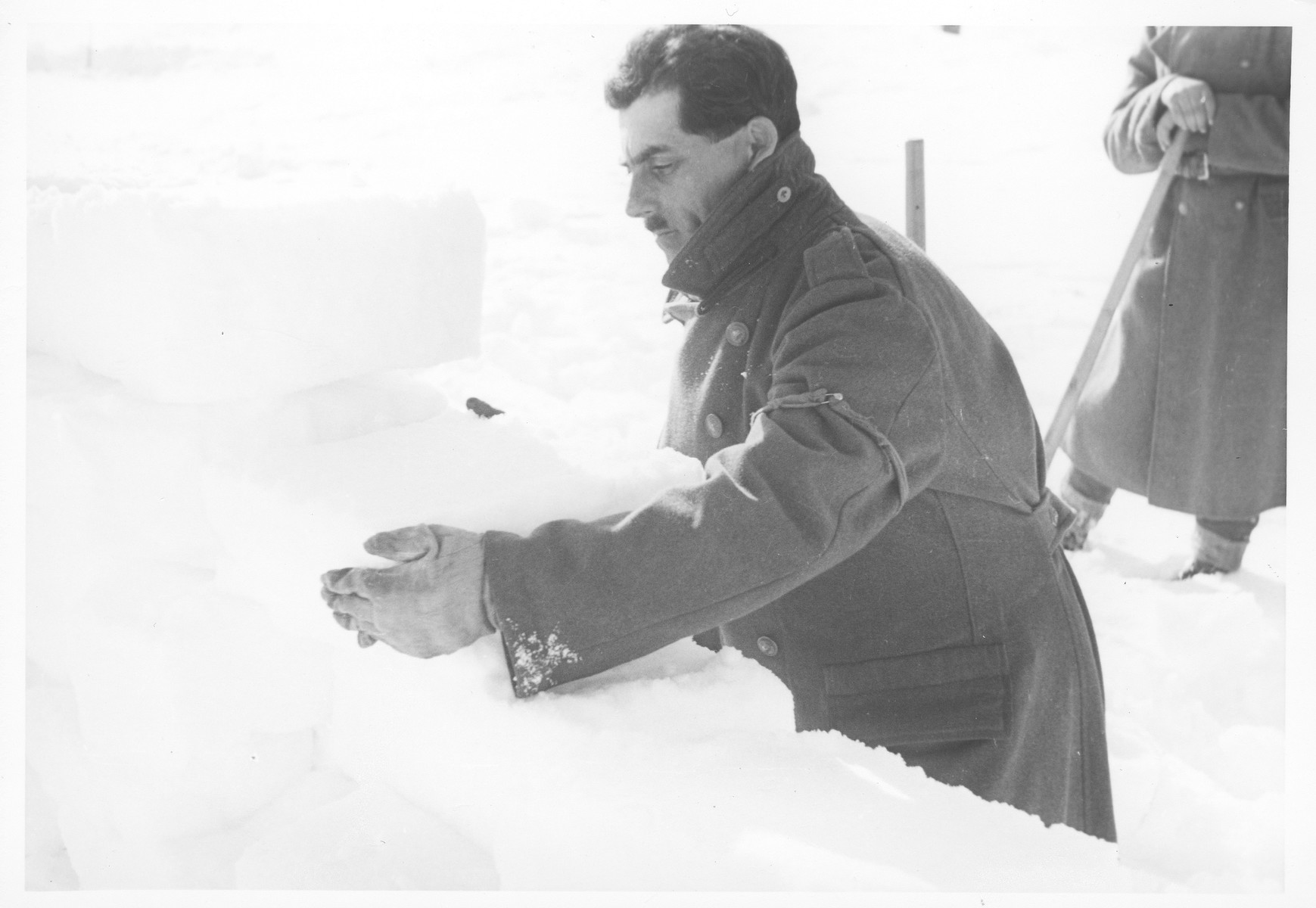 A Jewish conscript in Company 108/57 of the Hungarian Labor Service at forced labor clearing snow from a road.