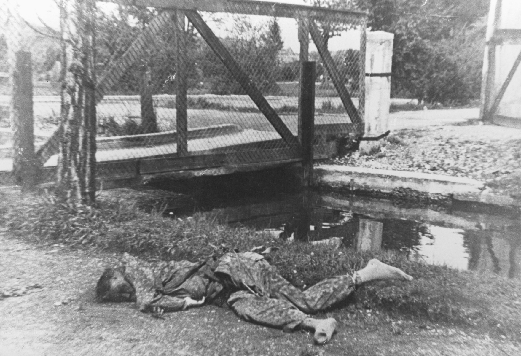 The body of an SS guard lies next to the moat in the Dachau concentration camp.