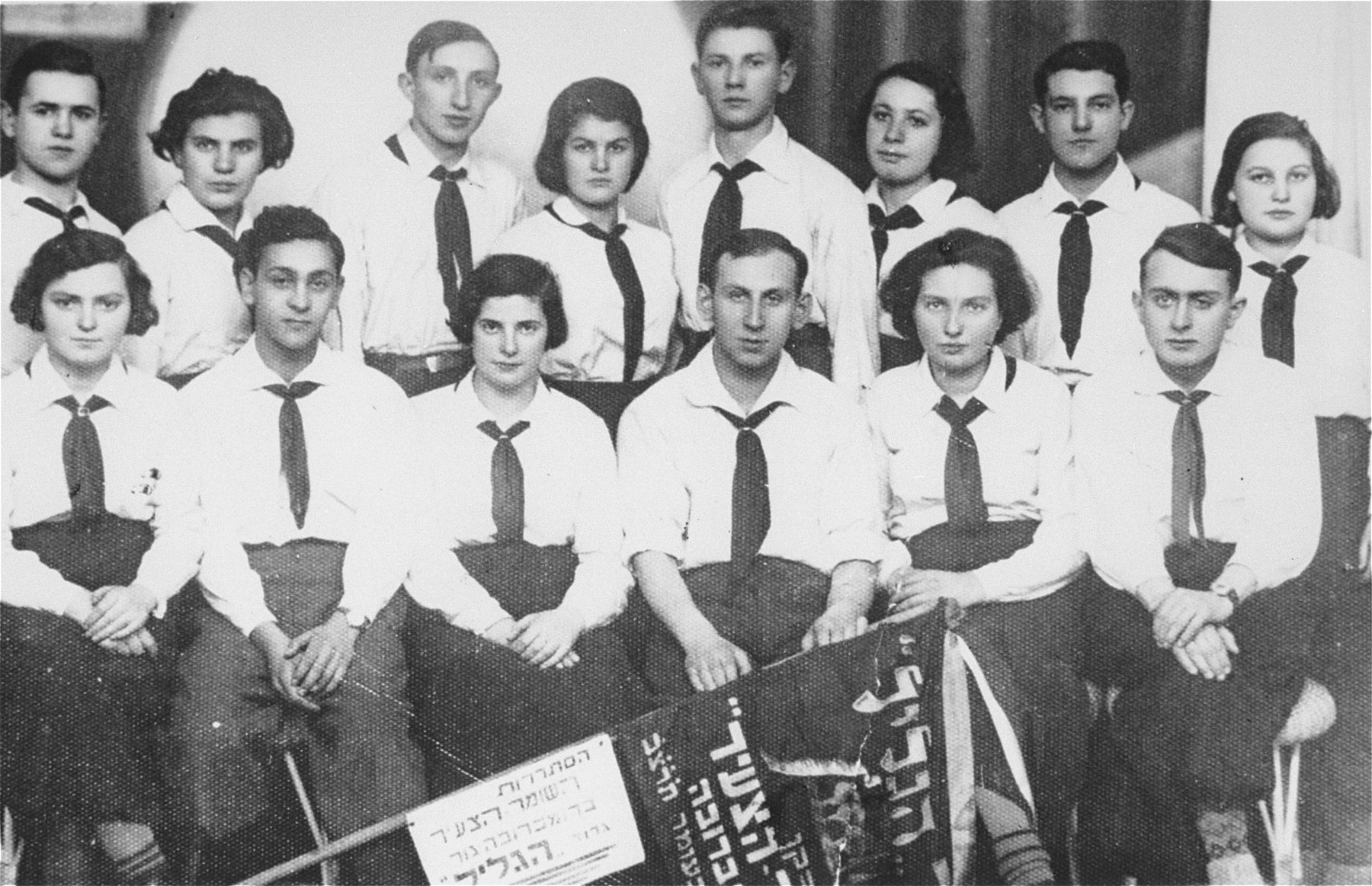 """A group portrait of """"Hagalil"""" unit of """"Hashomer Hatzair"""" Zionist youth organization in Dabrowa Gornicza.  Seated second from right, in the first row is Sala Rozen, donor's sister.   To her right are Isser Lemkowicz, Devorah (?) Kleiman and on the far right is Simen Rosenblum.  Third from the left standing is Lemul Lenkowicz and standing on the far right is Plawaes."""