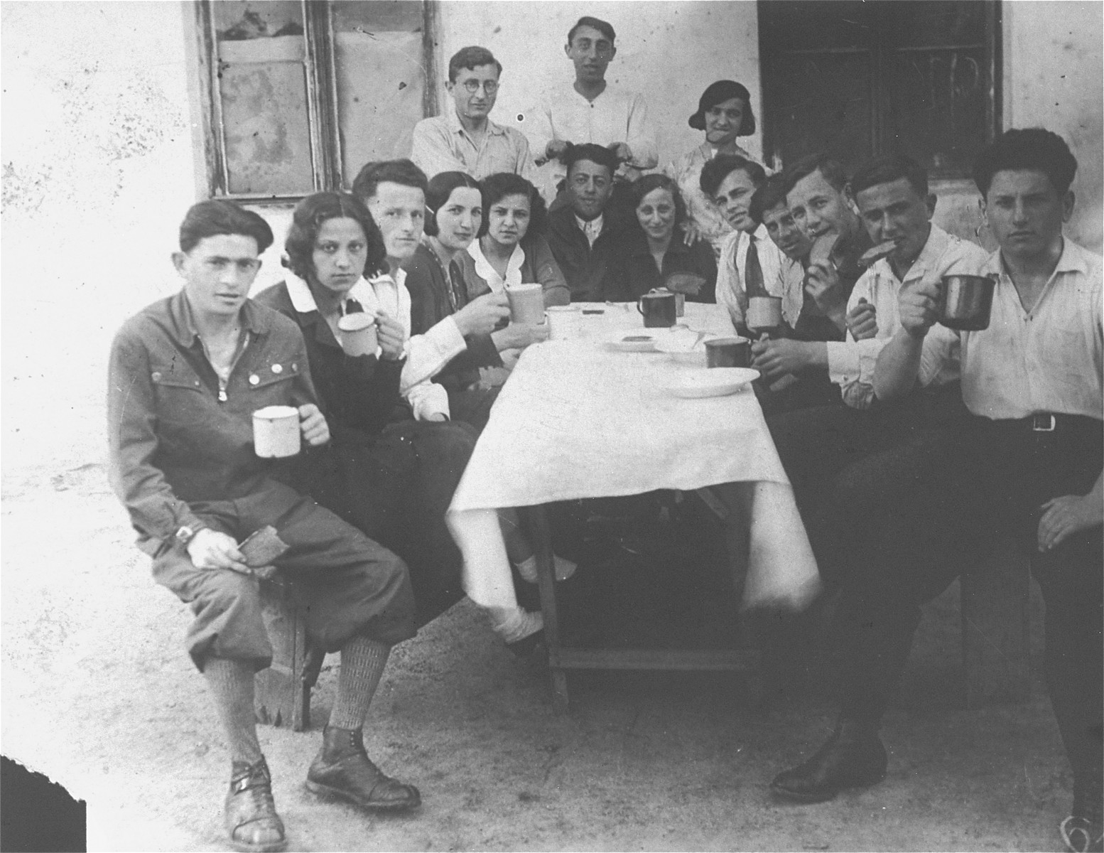 Members of a Zionist youth organization pose with coffee mugs around a table in Kolbuszowa.