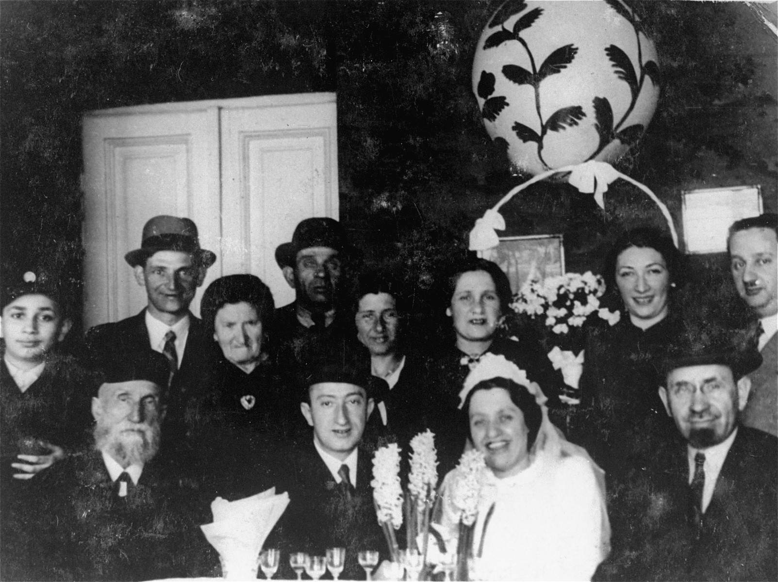 Group portrait of family and friends at the celebration following the wedding of Golda Weinstock and Shimon Zysblatt.    Among those pictured are the groom, Shimon Zysblatt, the bride, Golda Weinstock and the bride's father, Abraham Weinstock (bottom right). The bride is the donor's sister.