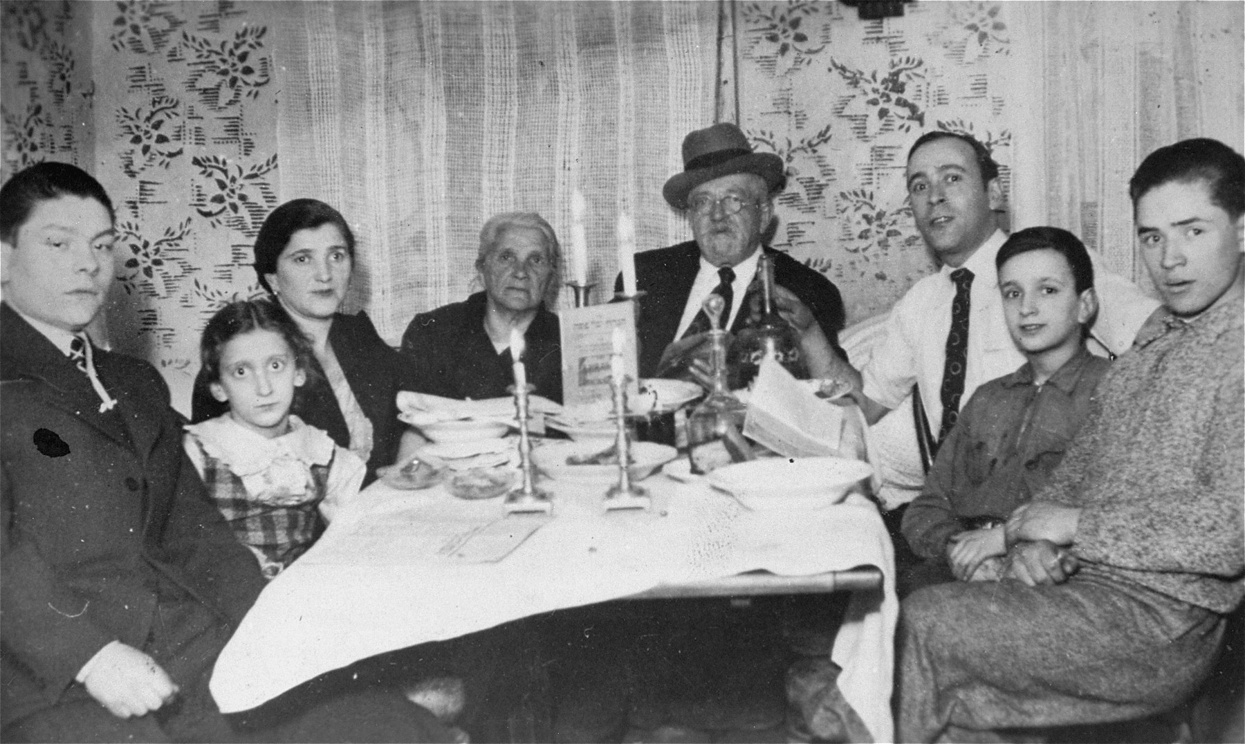 A Jewish family is gathered around the table during a Passover seder in their home in Vilna.  This was the family's last seder together before WWII.  Pictured from left to right are: unknown; Fruma Katz; Basia (Friedman) Katz; Chana Mina and Feivel Friedman; Mayer Katz; Chaskiel Katz and Theodore Friedman.