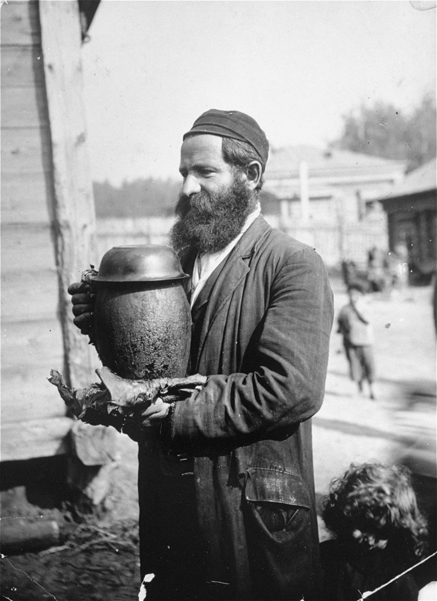 A Jew carries a pot of cholent [stew] to be cooked for the Sabbath.