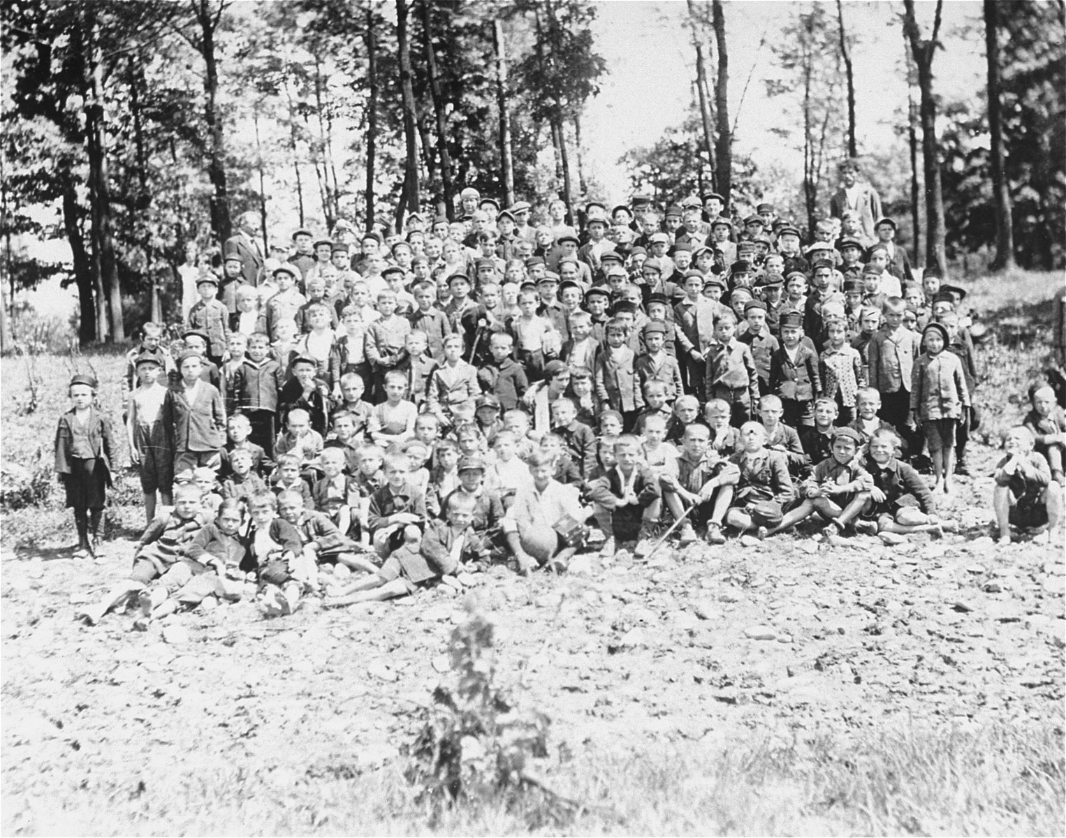 Group portrait of Jewish and non-Jewish children on a school outing in Oswiecim, Poland.   According to the donor, the boys wearing round dark caps are from Orthodox Jewish homes; the ones with flat caps are from less religious Jewish homes; and the ones with the four-cornered caps and without head covering are not Jewish.  The site of this outing was later Birkenau, part of the Auschwitz concentration camp.
