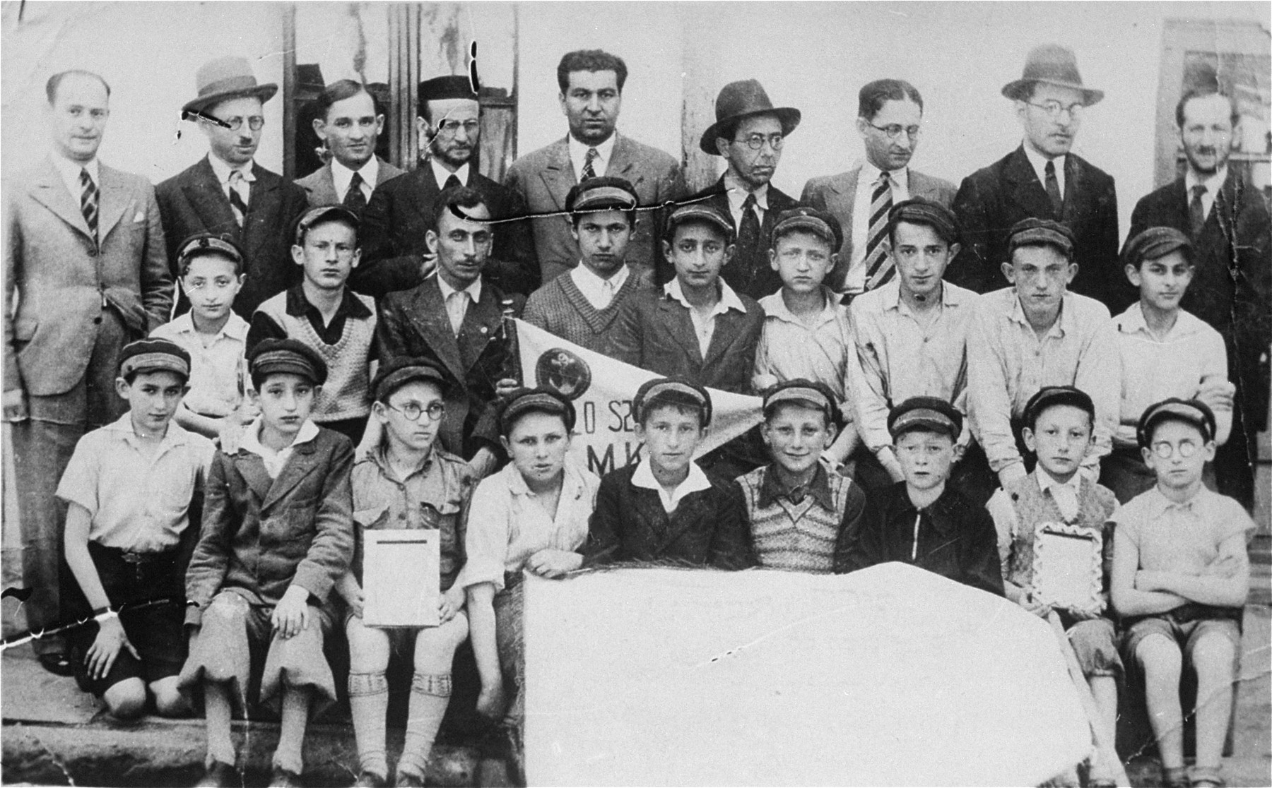 Group portrait of students and teachers of the Yavne Jewish religious elementary school for boys in Bedzin.   Among those pictured are: Motek Rechnic (second row from the front, third from the right) and Hesiek Zvi Rechnic (second row from the front, fifth from the right). Both of these children were from Dabrowa Gornicza.