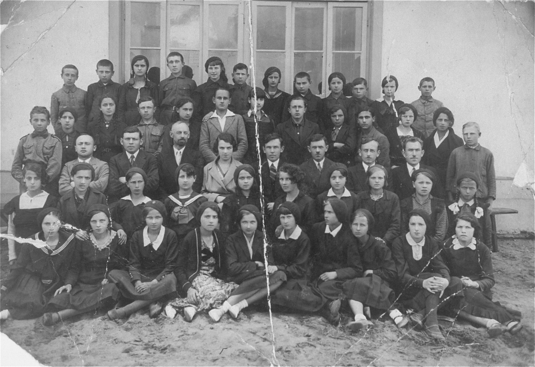 Group portrait of students and teachers in a public Polish high school in Wegrow, where many of the students were Jewish.    Wladyslaw Wojcik is pictured standing in the last row, first on the left.