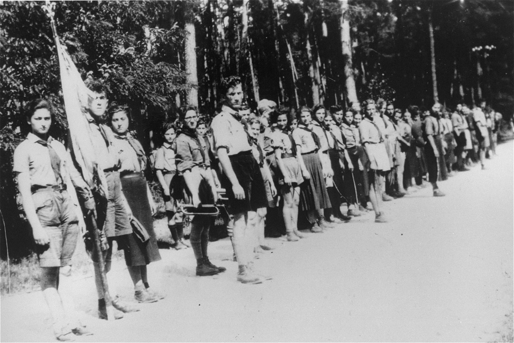 Members of the Hashomer Hatzair Zionist youth movement stand in formation along a road, several of them holding musical instruments.  Among those pictured is Meyer Zarnowiecki (holding a trumpet).