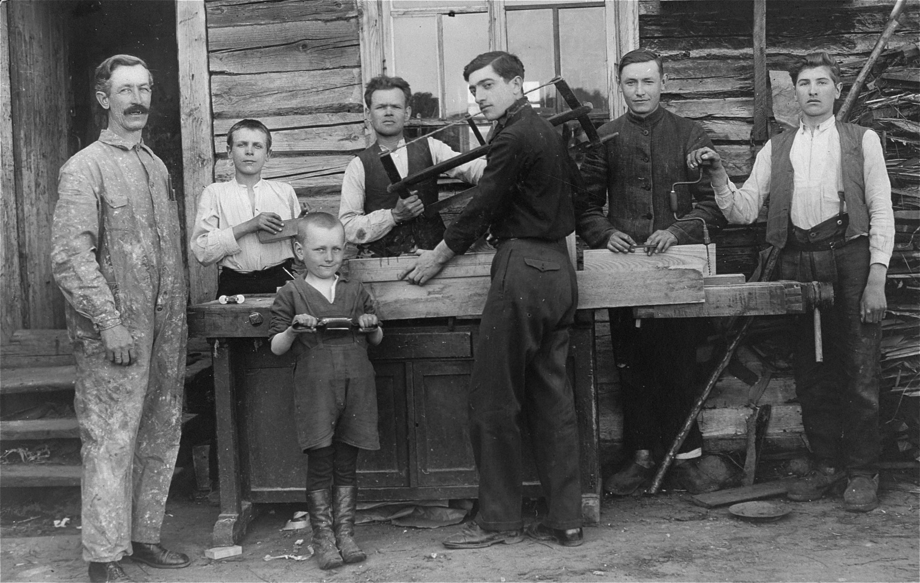 Members of a hachshara (Zionist collective) in Lithuania learn carpentry.  Pictured in the center is Eliezer Kaplan.
