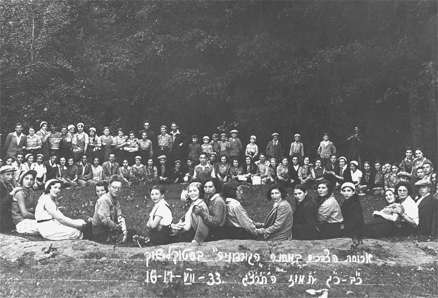 Jewish youth attend the summer camp of the Zionist Gordonia movement in Stoklishok, Lithuania.  Participants are gathered outside for lunch.