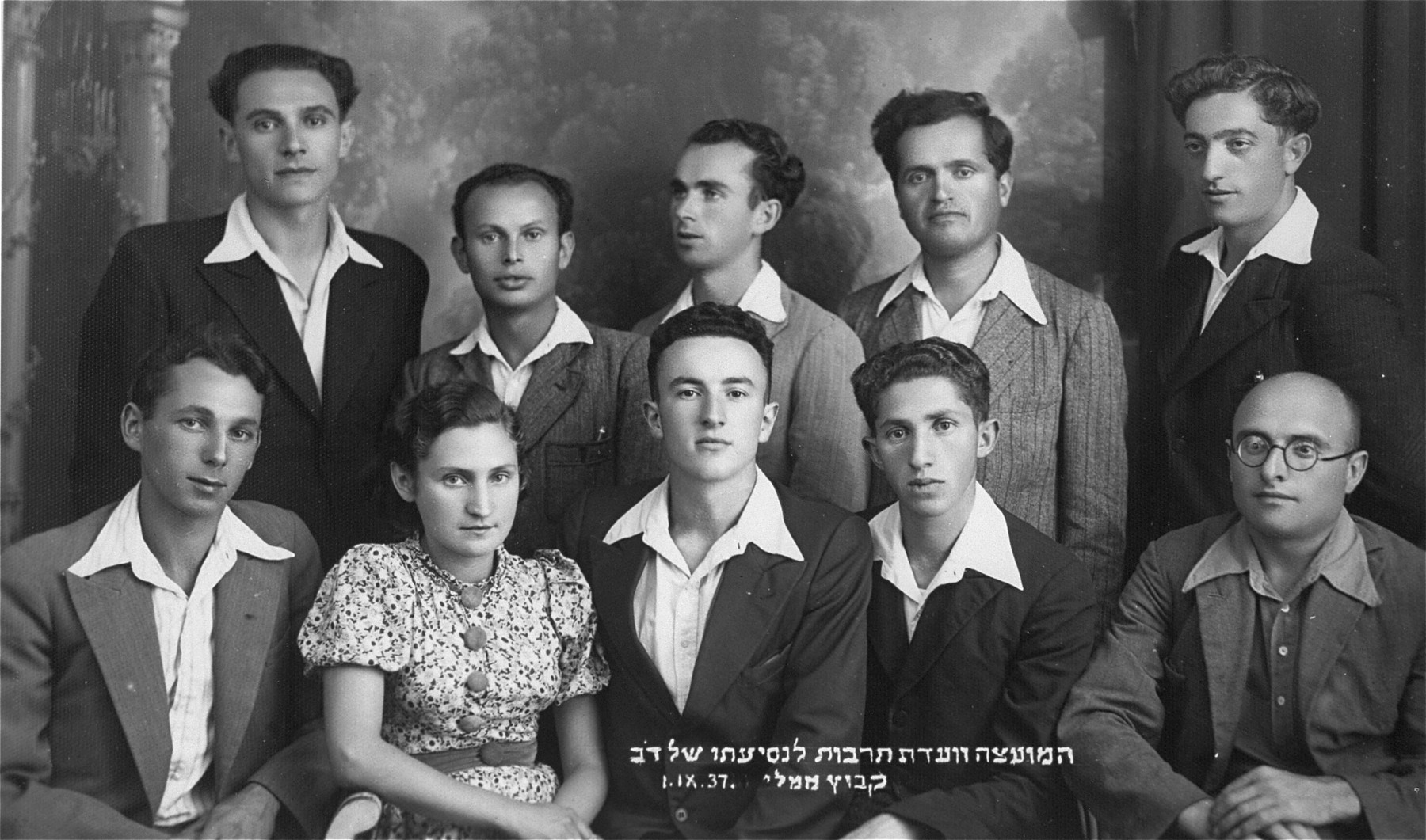 Group portrait of the cultural committee of the kibbutz hachshara, Bemaaleh, taken on the occasion of the departure of one of its members.  Pictured standing at the far right is Eliezer Kaplan, the donor's father.