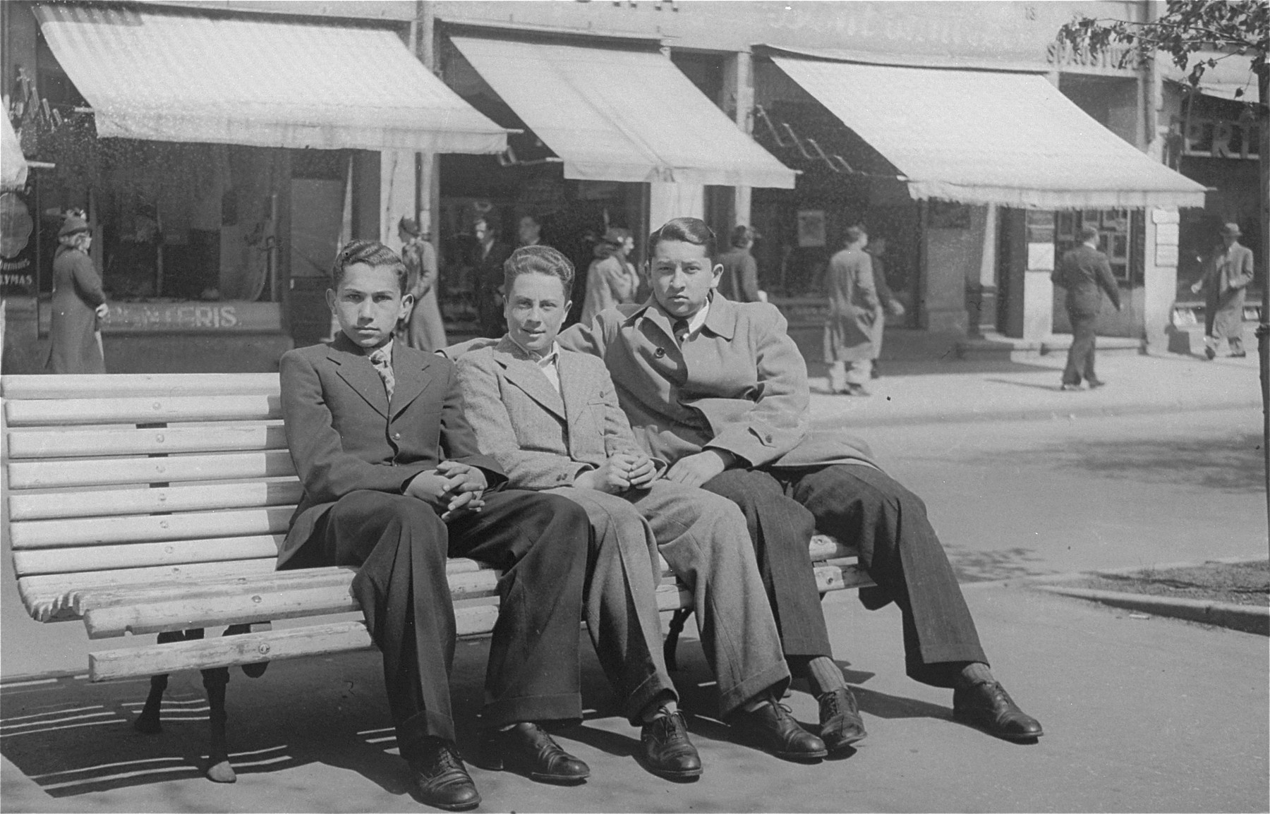 Three Jewish students sit on a street bench in Kovno.  Among those pictured is Jascha Polunski (center).
