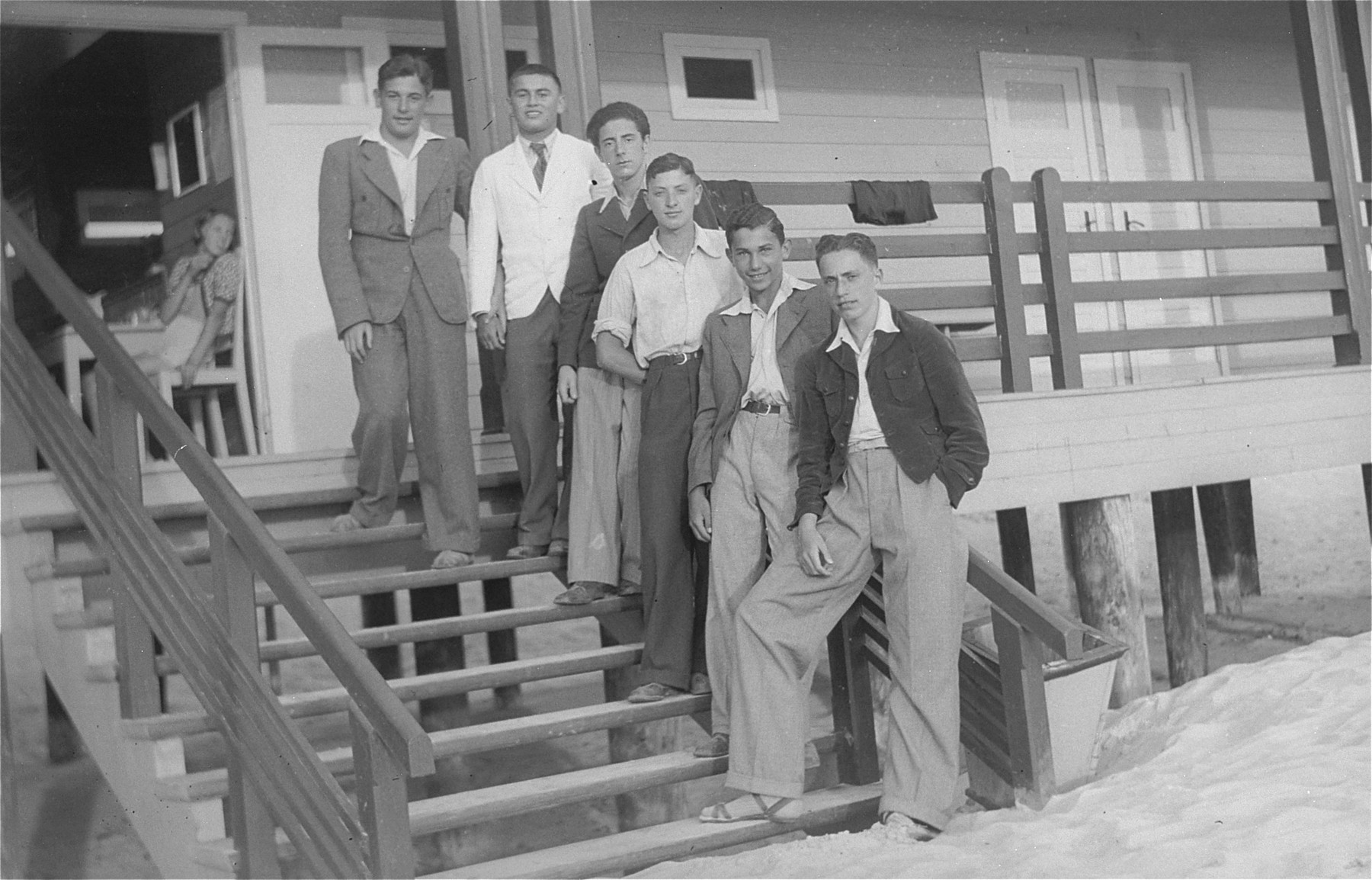 A group of Jewish youth pose on the stairs of a boathouse.