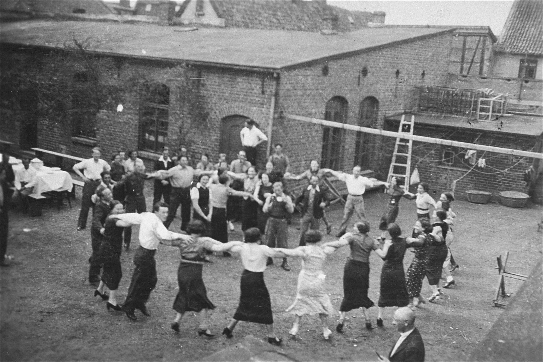 Members of a Zionist collective in Lithuania dance outside in a courtyard during a Shavout holiday celebration.