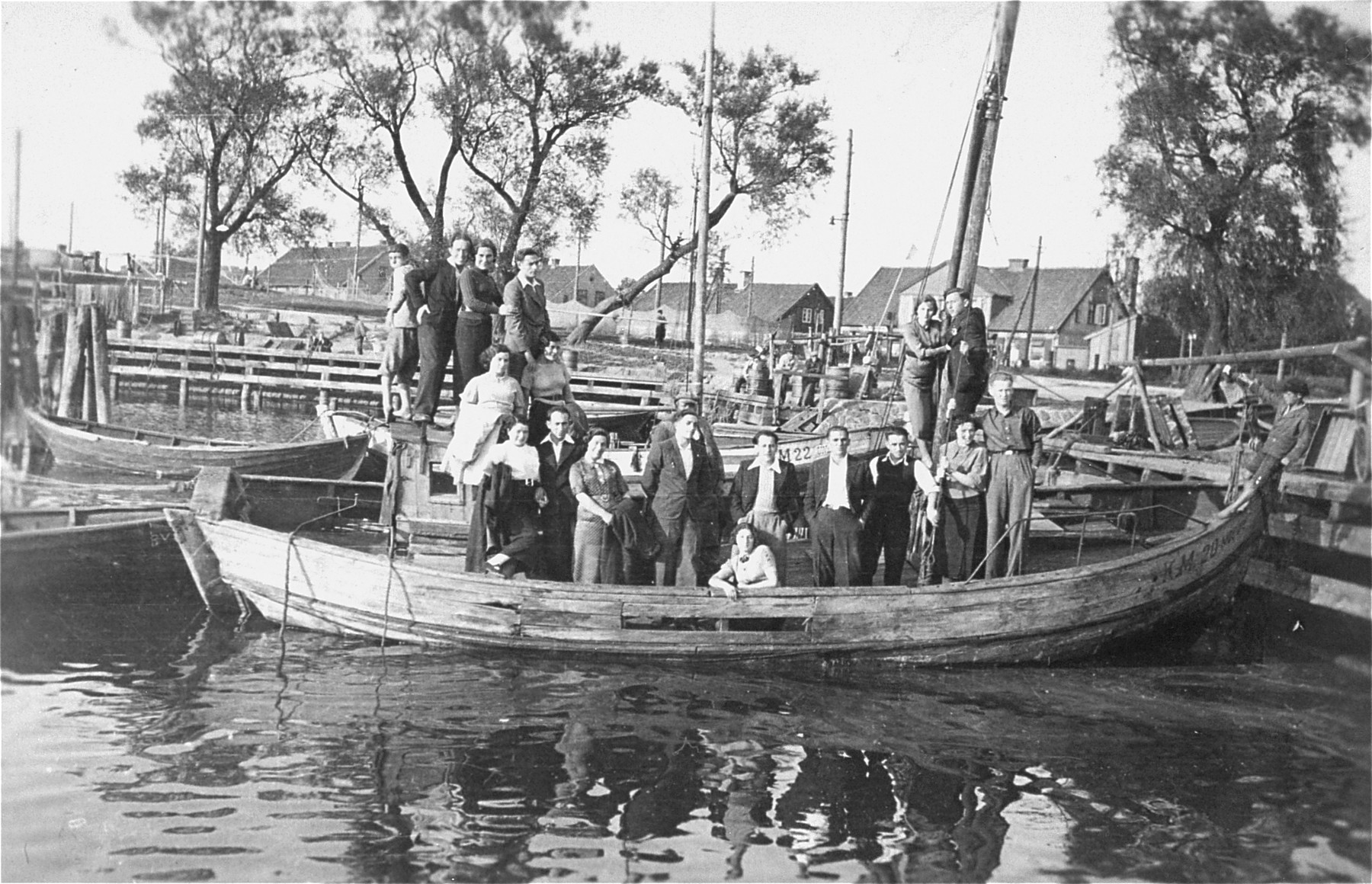 Eliezer Kaplan poses with friends from the Zionist movement in a fishing boat anchored at a small boating dock in a Lithuanian village.