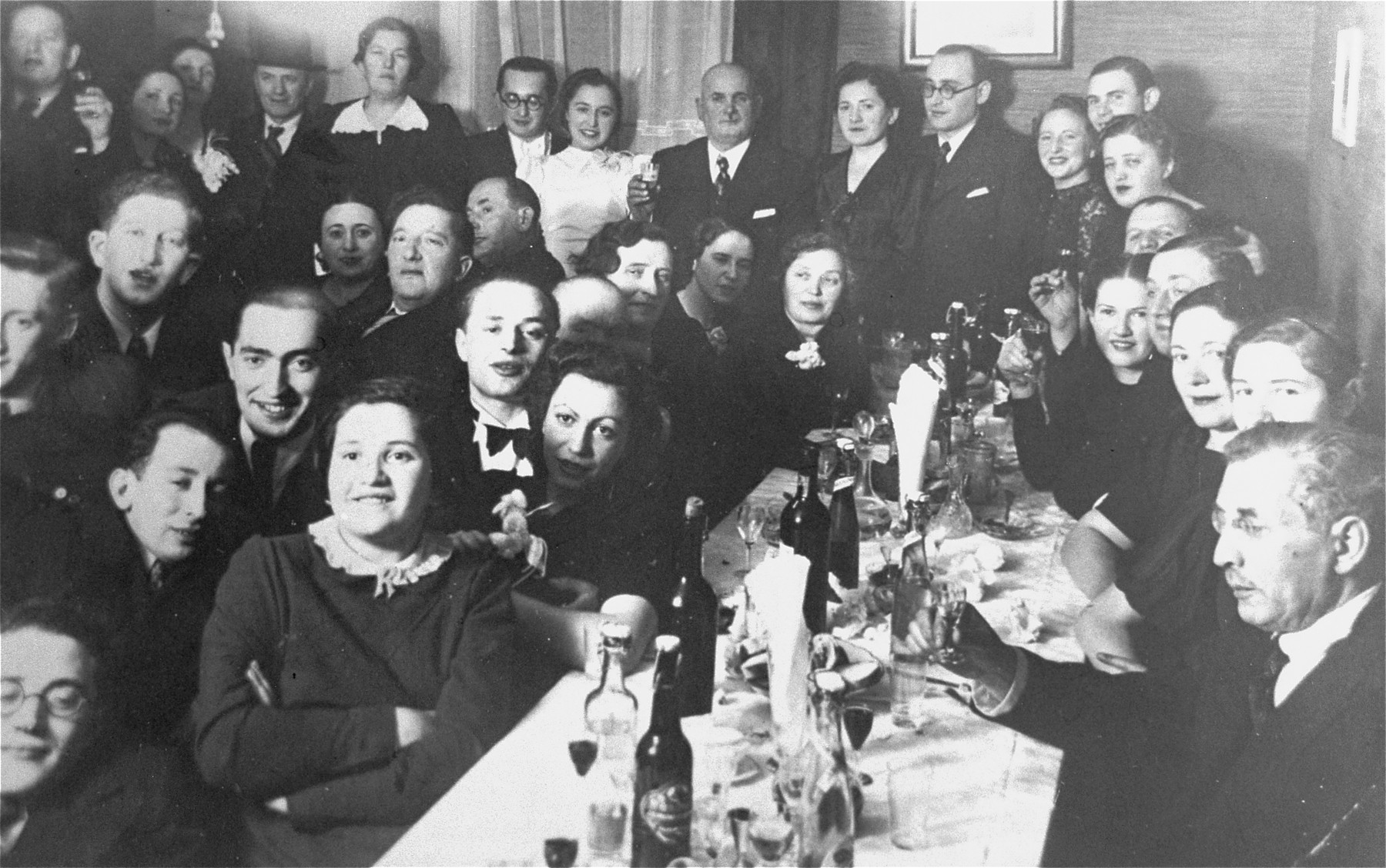 Family and friends are gathered for a Jewish wedding celebration in Kovno.  Among those pictured are Jona and Gita Wisgardisky (standing at the back on the right).