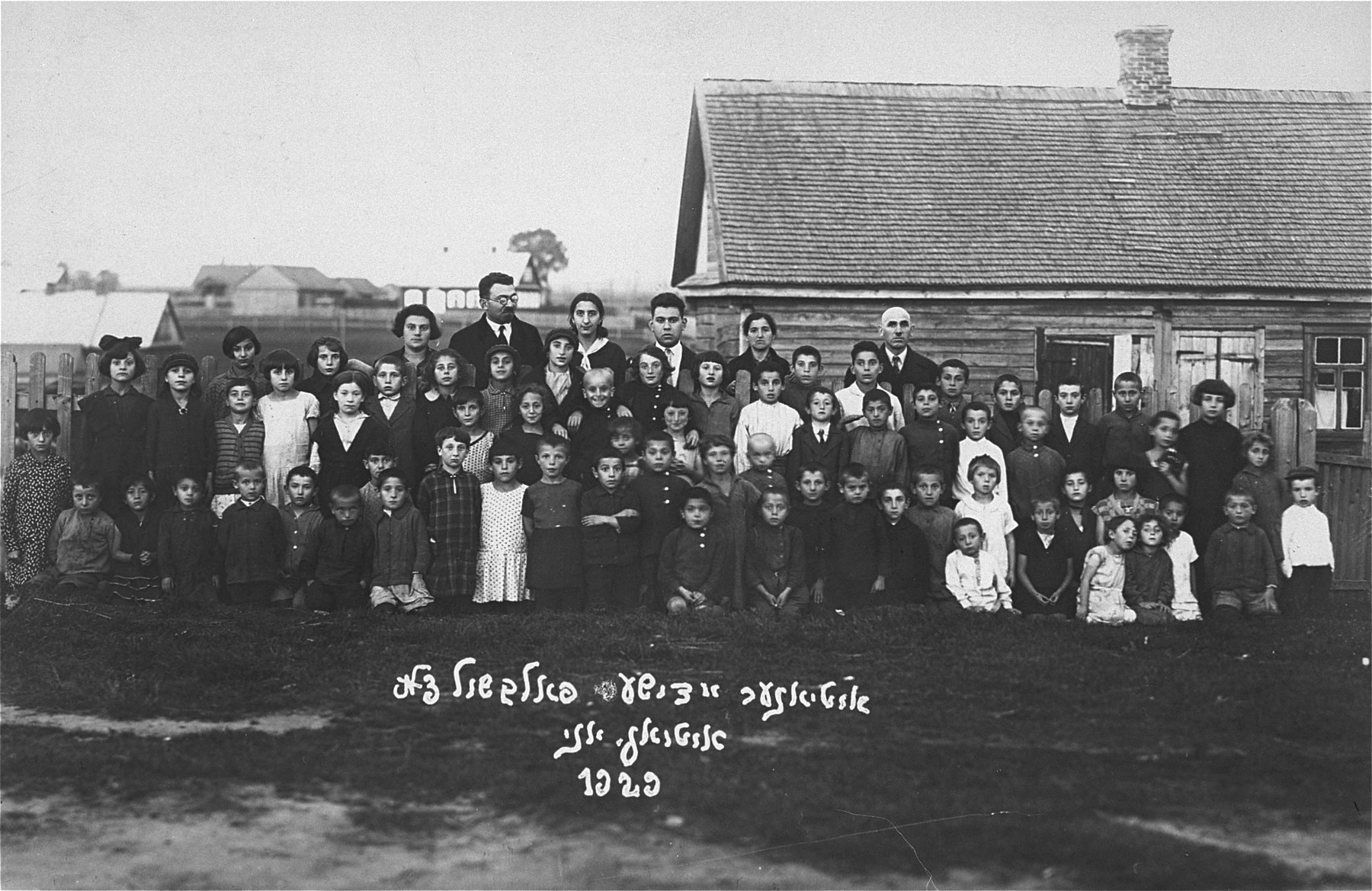 Group portrait of the students and teachers of the Jewish Volksschule (elementary school) in Utena.   Pictured in the back row, center, is Joseph Gar.