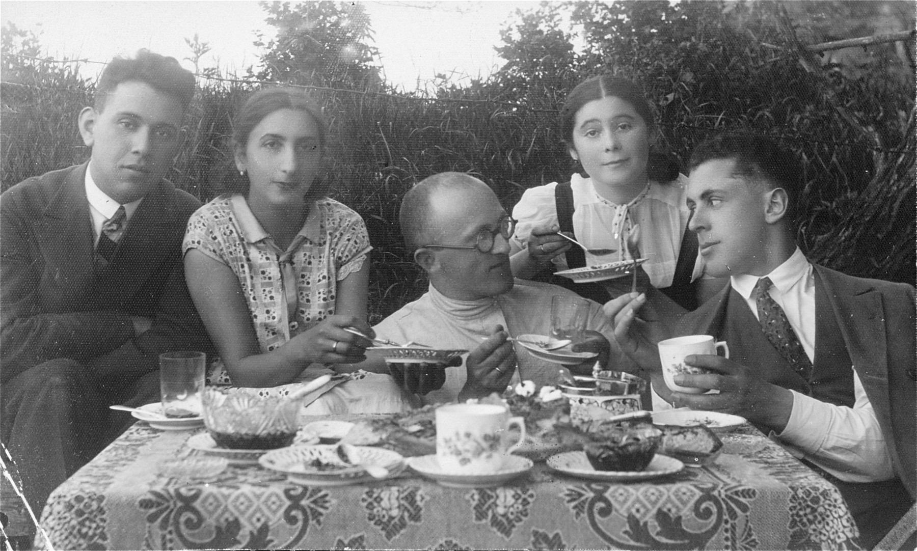 A group of young teachers from the Jewish Volksschule (elementary school) no.3 in Utena, socialize over tea taken outside in front of the school.  Pictured at the far left is Joseph Gar, the donor's uncle.