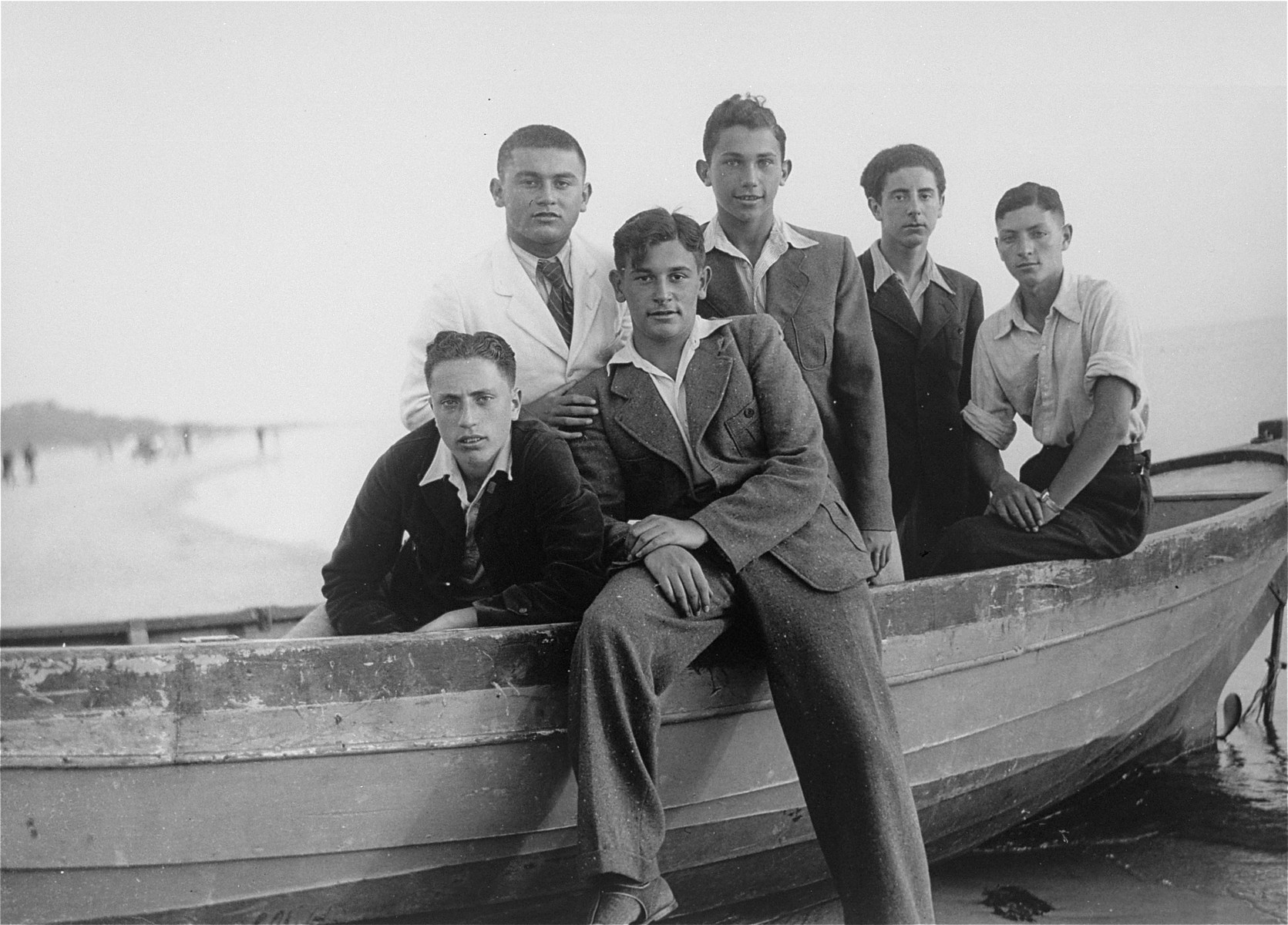 Five Jewish youth pose in a row boat at a vacation spot in Lithuania.