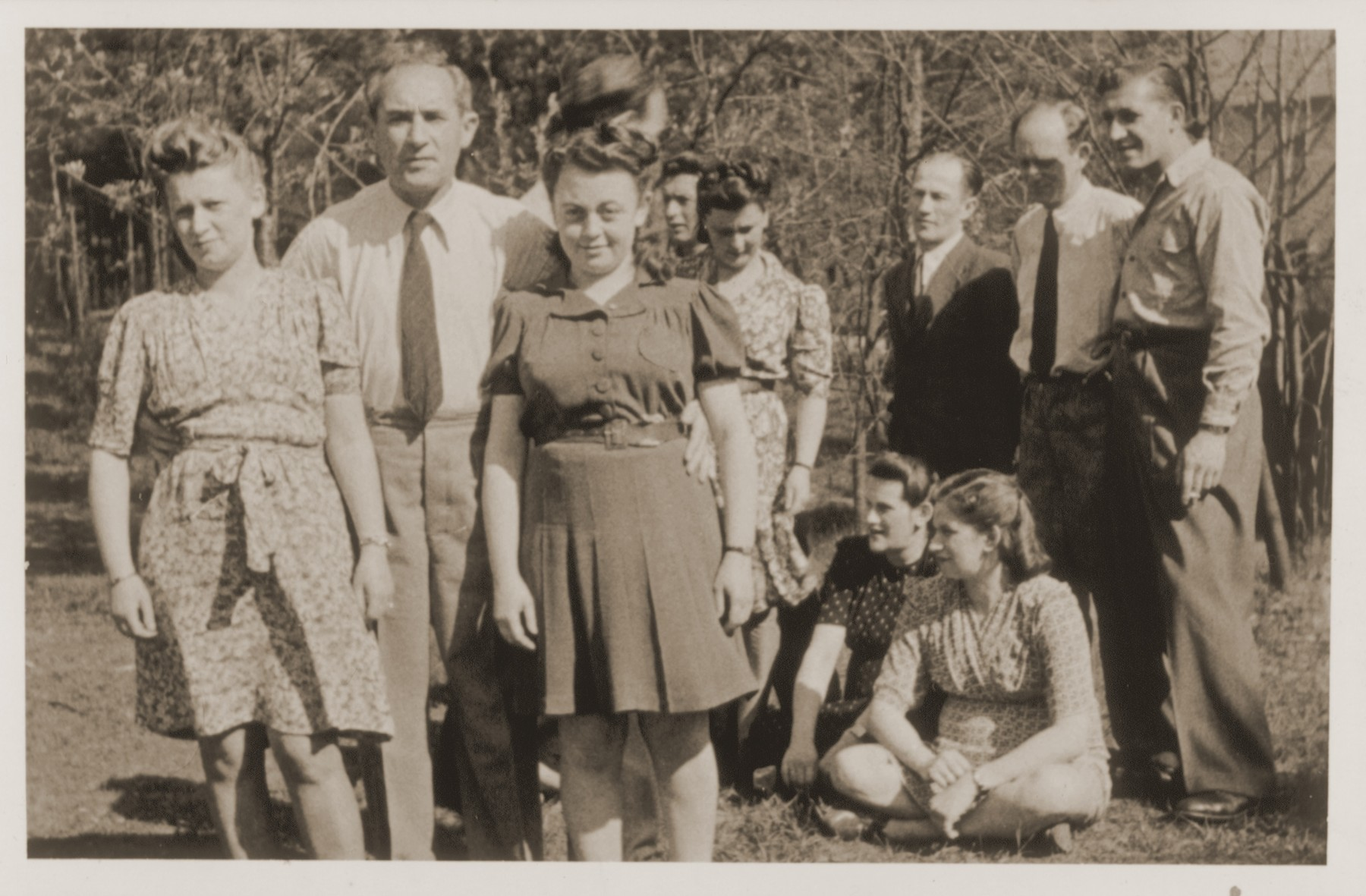 "A group of Jewish DPs at the Schlachtensee displaced persons camp.    Standing from left to right are: Guta Tencer, Moses Tencer, Chana Tencer, Pola Zyngier, Moshe Frymerman, Rachmiel Zyngier, and unidentified.  Seated from left to right are: Renia (Kilman) Frymerman and Eva (Kilman) Zyngier.  Verso is signed ""Hania."""