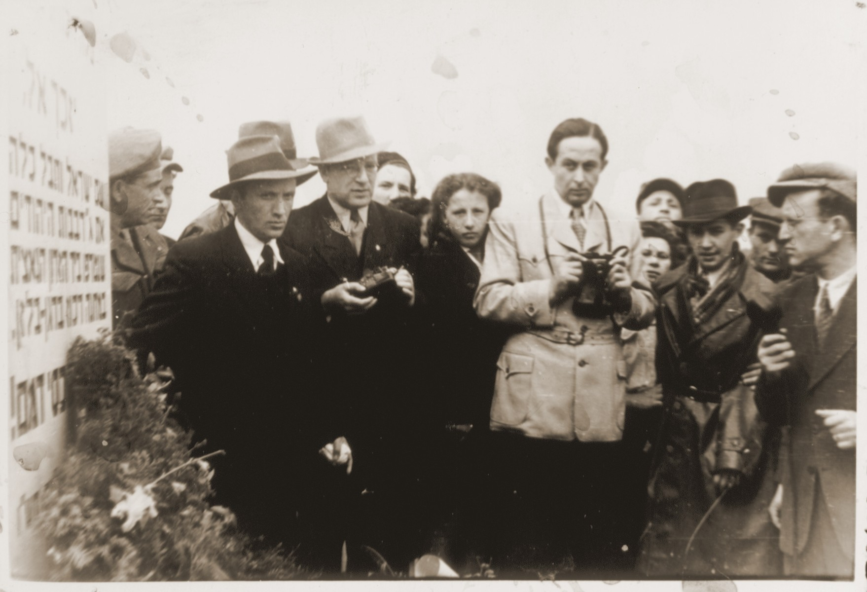 A group of Jewish DPs stand near the memorial at the Bergen-Belsen concentration camp.    Among those pictured are Roniek Zyngier (right) and Lolek Rosenblatt (center, with a camera slung around his neck).